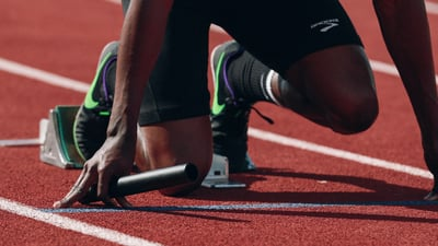 A sprinter kneels on the track with a baton in hand in preparation for a relay race