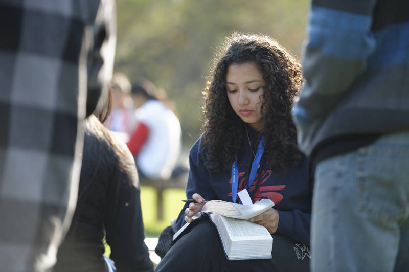 A young woman studies while attending a FSY conference.