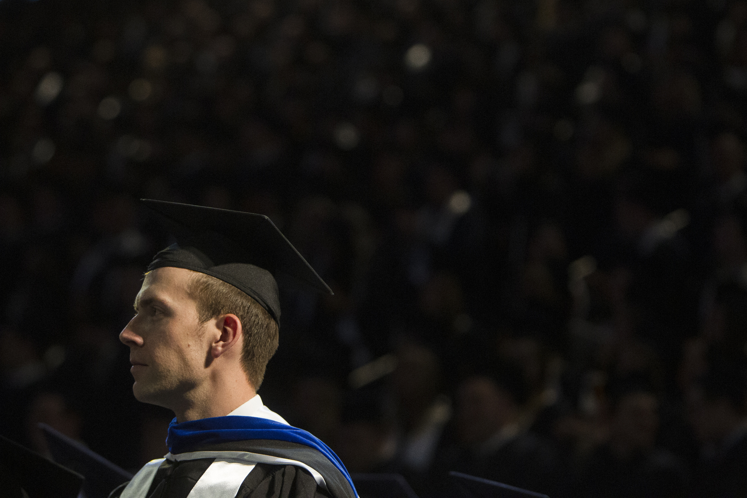 BYU graduate Jared Thomas, of Cottonwood Heights, watches the proceedings during Brigham Young University's commencement ceremony in the Marriott Center on Thursday, April 26, 2018, in Provo. BYU is awarding nearly 6,300 degrees to graduates this week.