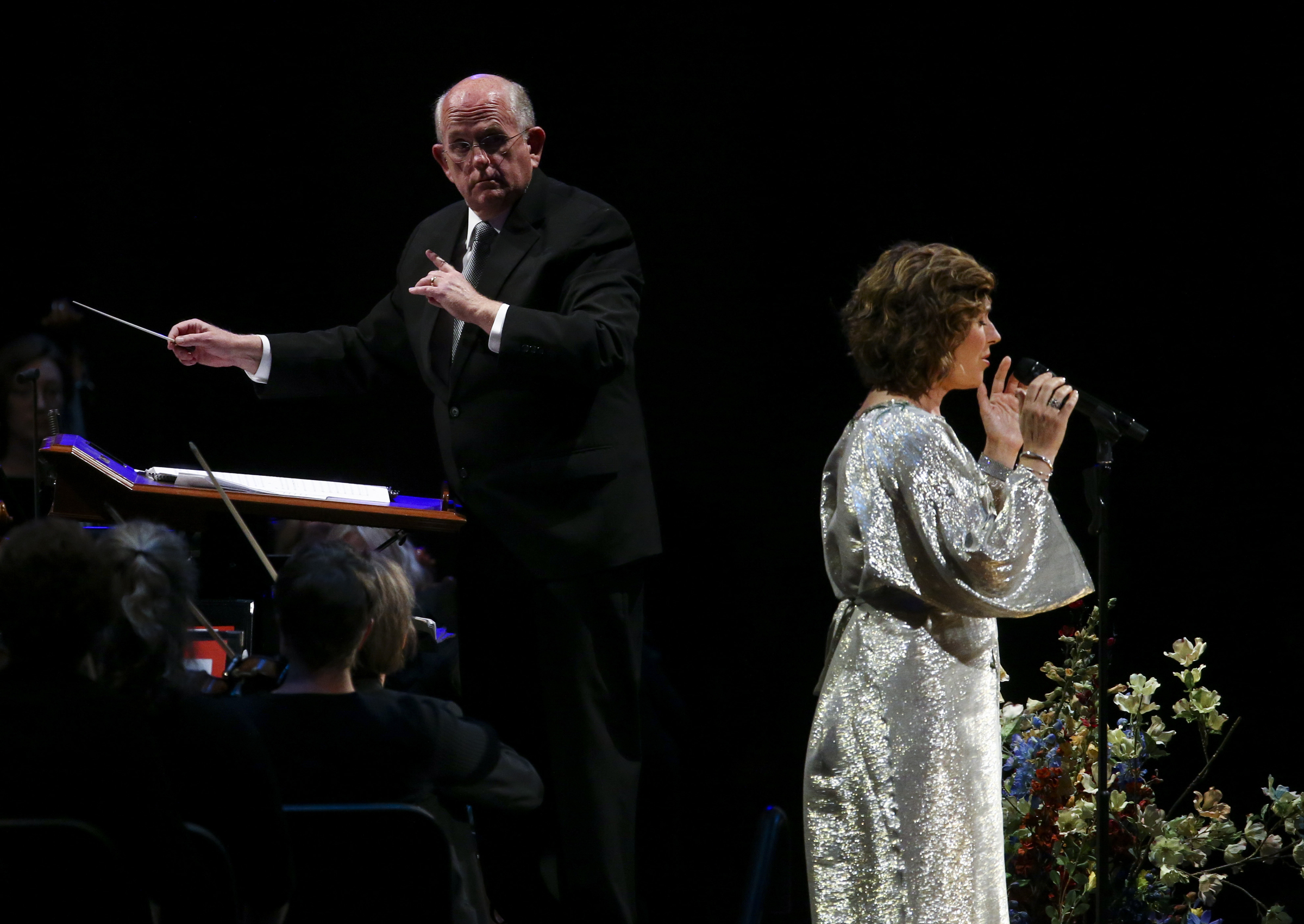 Conductor Mack Wilberg looks back at special guest Sissel as she sings with the Tabernacle Choir and Orchestra at Temple Square during the Pioneer Day concert at the Conference Center in Salt Lake City on Friday, July 19, 2019.