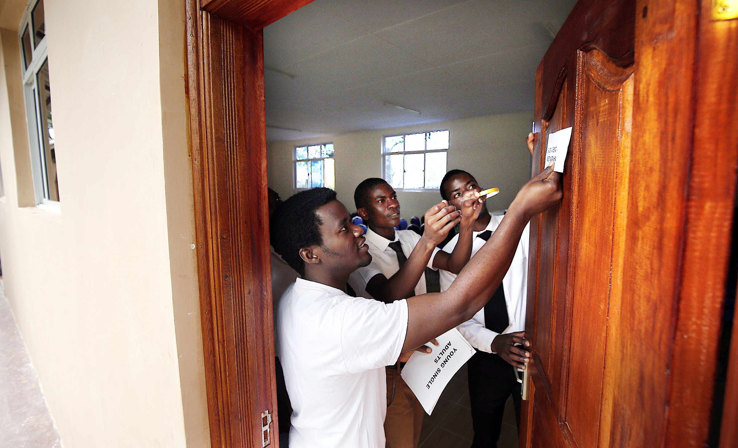 Robinson Imende, left, Jeff Busutu and Samuel Mburu put up a sign to show where sacrament meeting will be held during an open house at the Rongai meetinghouse on the outskirts of Nairobi on Saturday, April 14, 2018.