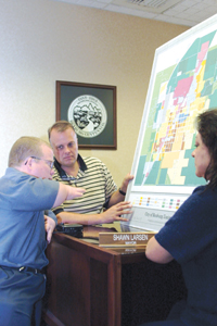 Mayor Shawn Larsen, center, talks with Brian Dale of HUD and Gloria Mabbutt, state rural development manager.