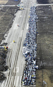 Vehicles washed away during the March 11 tsunami are collected beside a runway of Sendai Airport in Sendai, Miyagi Prefecture, Japan, Wednesday March 23, 2011.