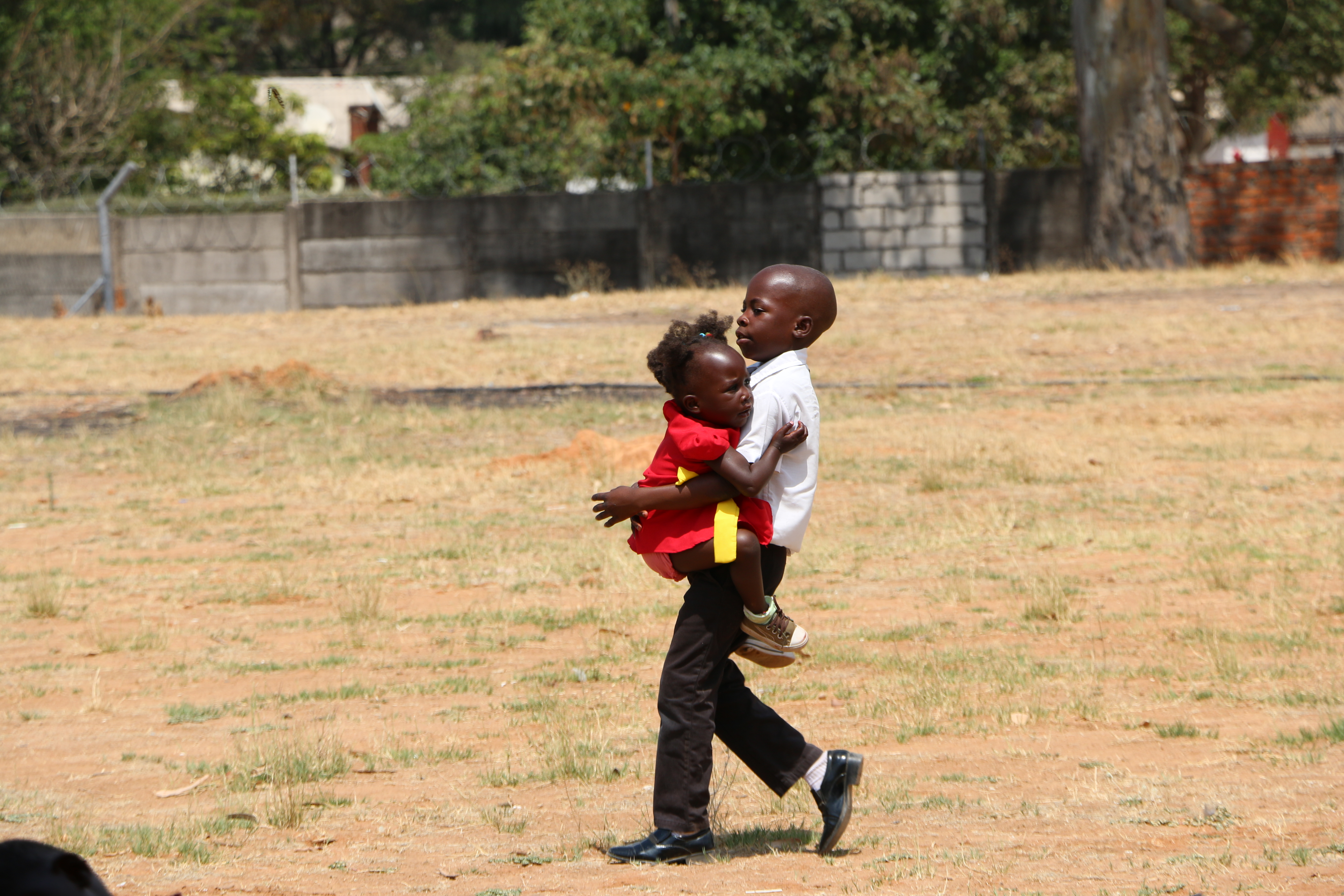 A young boy carries his sister into a member meeting in Zimbabwe on Nov. 18. 2018.