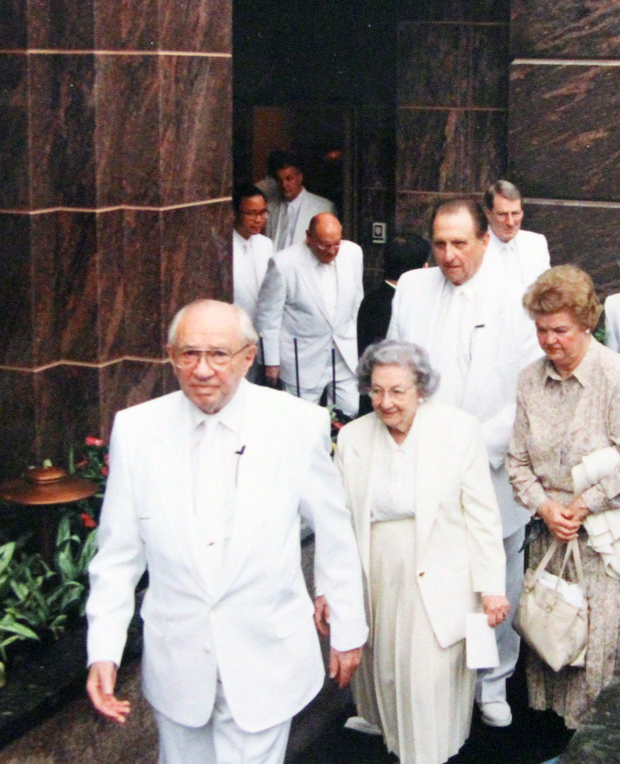 President Gordon B. Hinckley, Sister Marjorie P. Hinckley, President Thomas S. Monson, Sister Frances J. Monson and others walk out of the Hong Kong Temple to participate in its cornerstone ceremony on May 26, 1996.