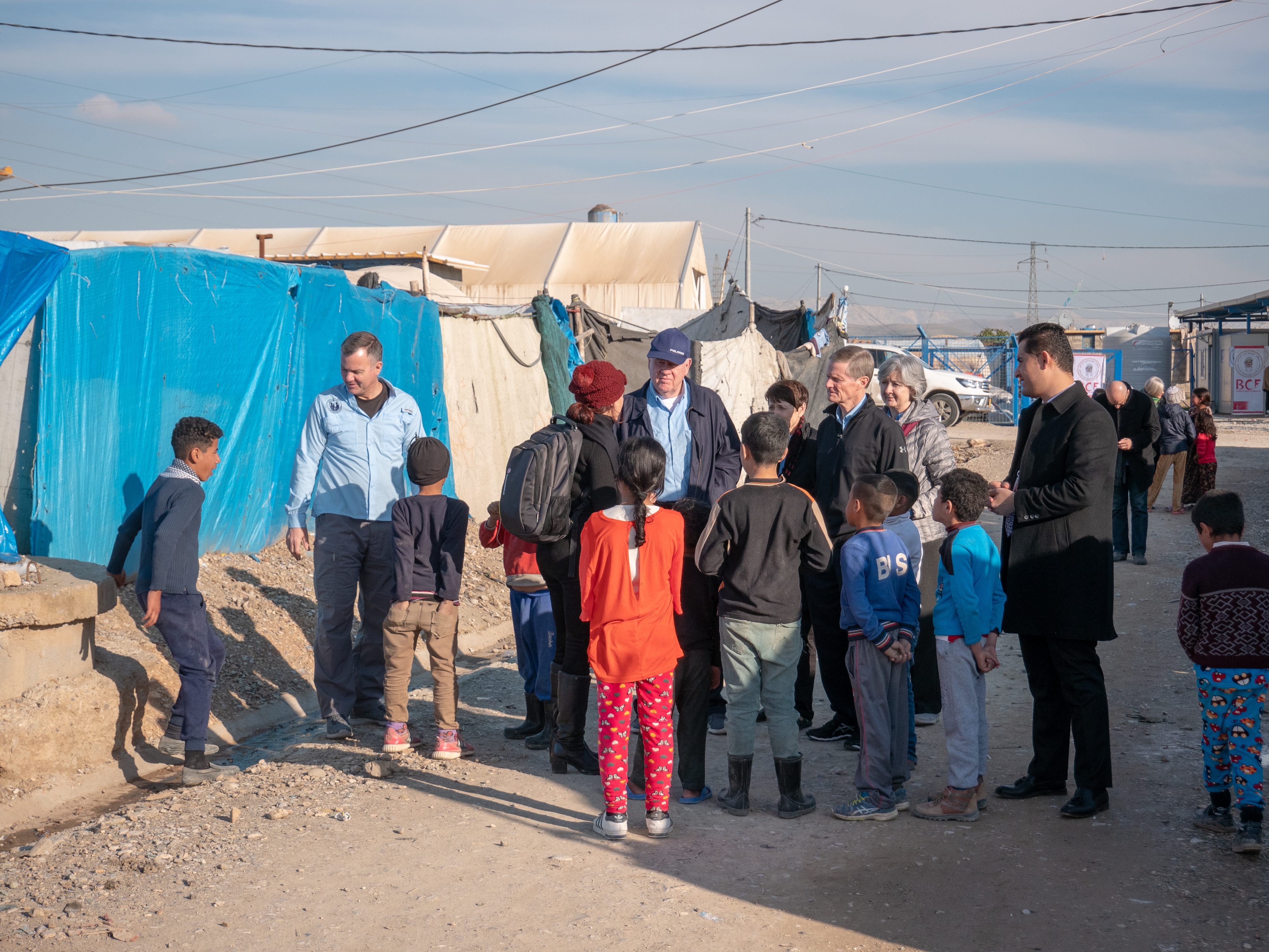 A group of visitors — including Elder David A. Bednar, Sister Susan Bednar, Elder Wllford W. Andersen and Sister Kathleen Andersen —are greeted by children at the Ashti refugee camp near Erbil, Kurdistan, on Jan. 21, 2019. LDS Charities assisted in 750 tents in two refugee camps in the area.