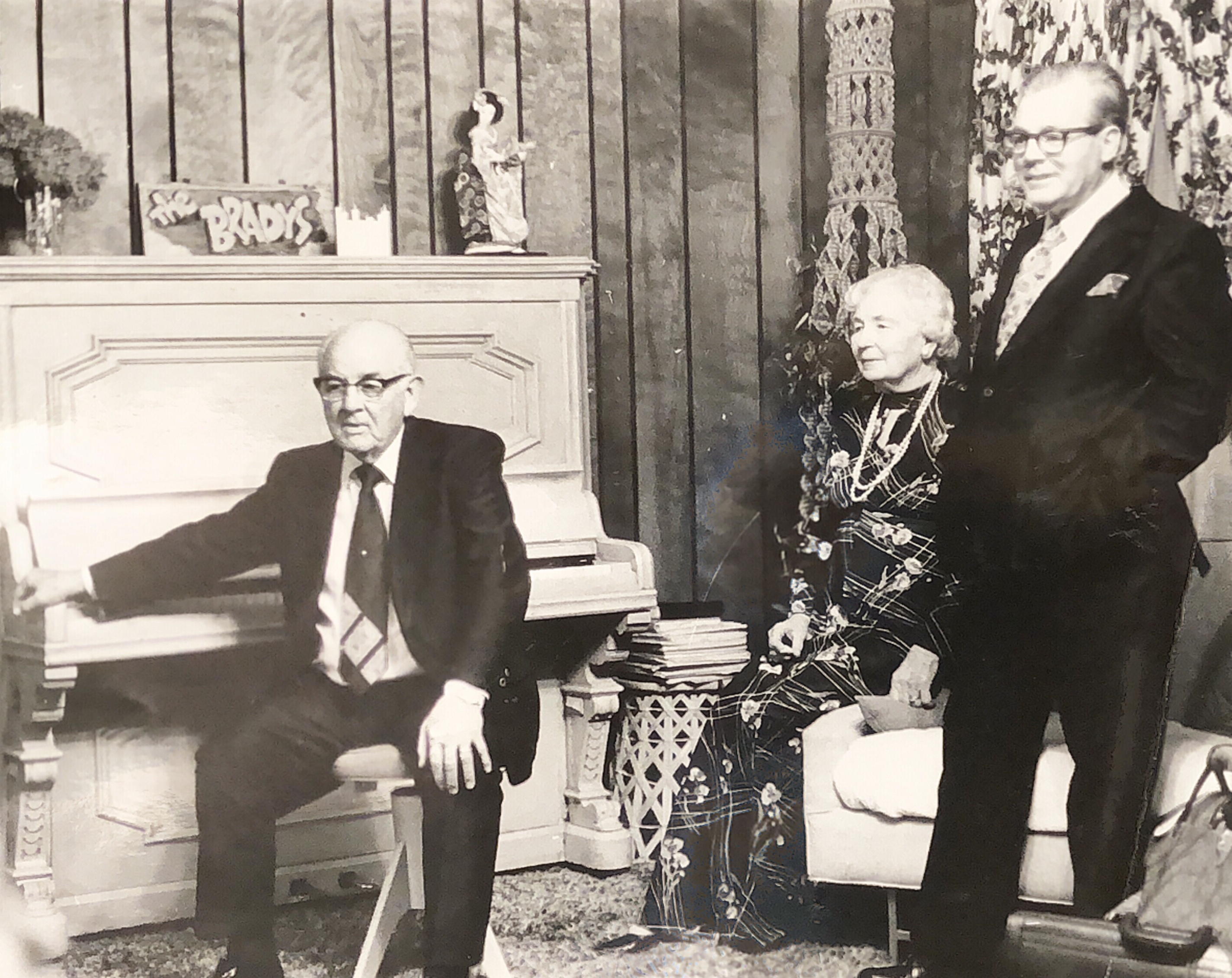 "While visiting the home of Robert and Glenda Brady in 1975, President Spencer W. Kimball chose to sit on an old-fashioned piano stool. After a few minutes, he whirled around and played ""I Am a Child of God."" In the photo are Sister Camilla Kimball and D. Arthur Haycock, President Kimball's executive secretary."