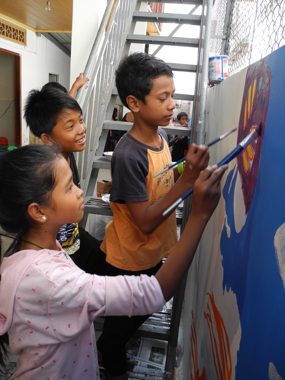 In a project organized by Elder Gerrit W. Gong and his family, children in Phnom Pehn, Cambodia, paint a mural on the wall of a soup kitchen.