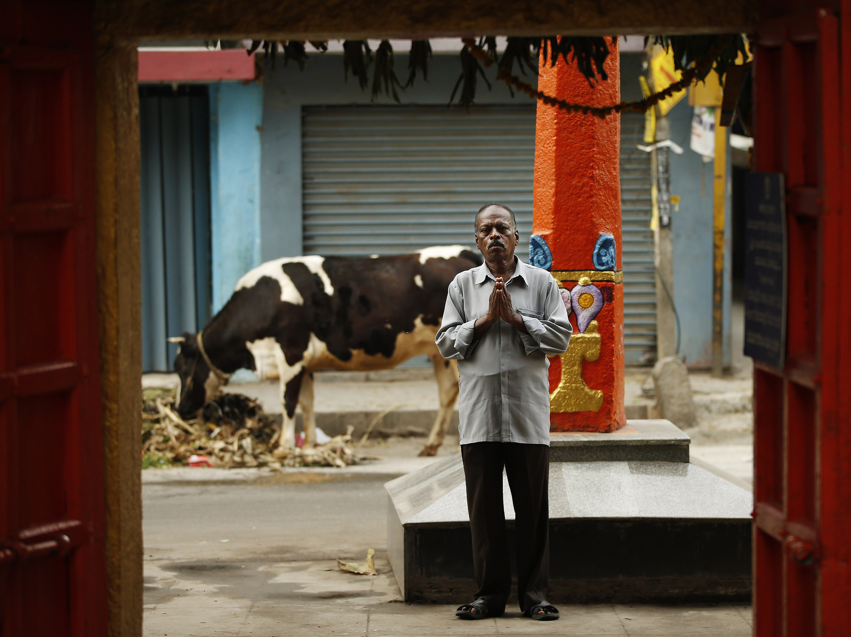 A man prays at a Hindu temple as a cow eats in a street in Bengaluru, India, on Thursday, April 19, 2018.