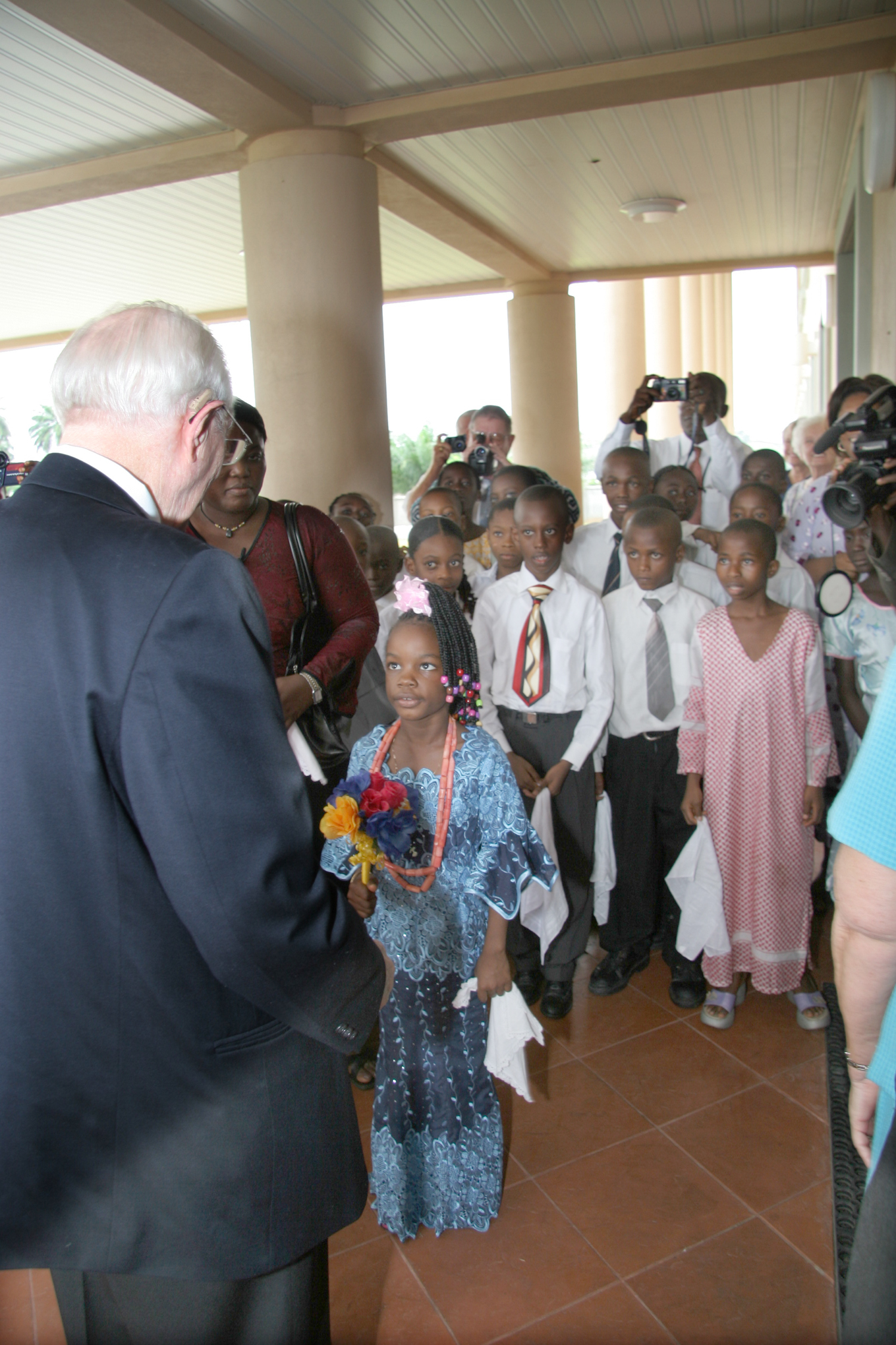 Amarachi Kamu-chukwuma, 6 years old, handing a bouquet of flowers to President Gordon B. Hinckley on Aug. 5, 2005, upon his arrival at Aba Nigeria Temple grounds.