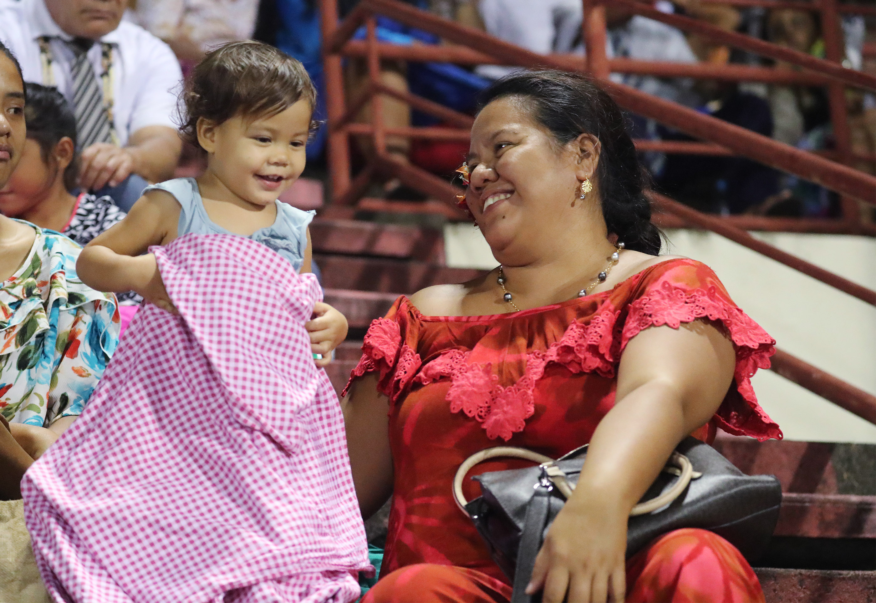 An attendee plays with her child during a devotional in Papeete, Tahiti, on May 24, 2019.