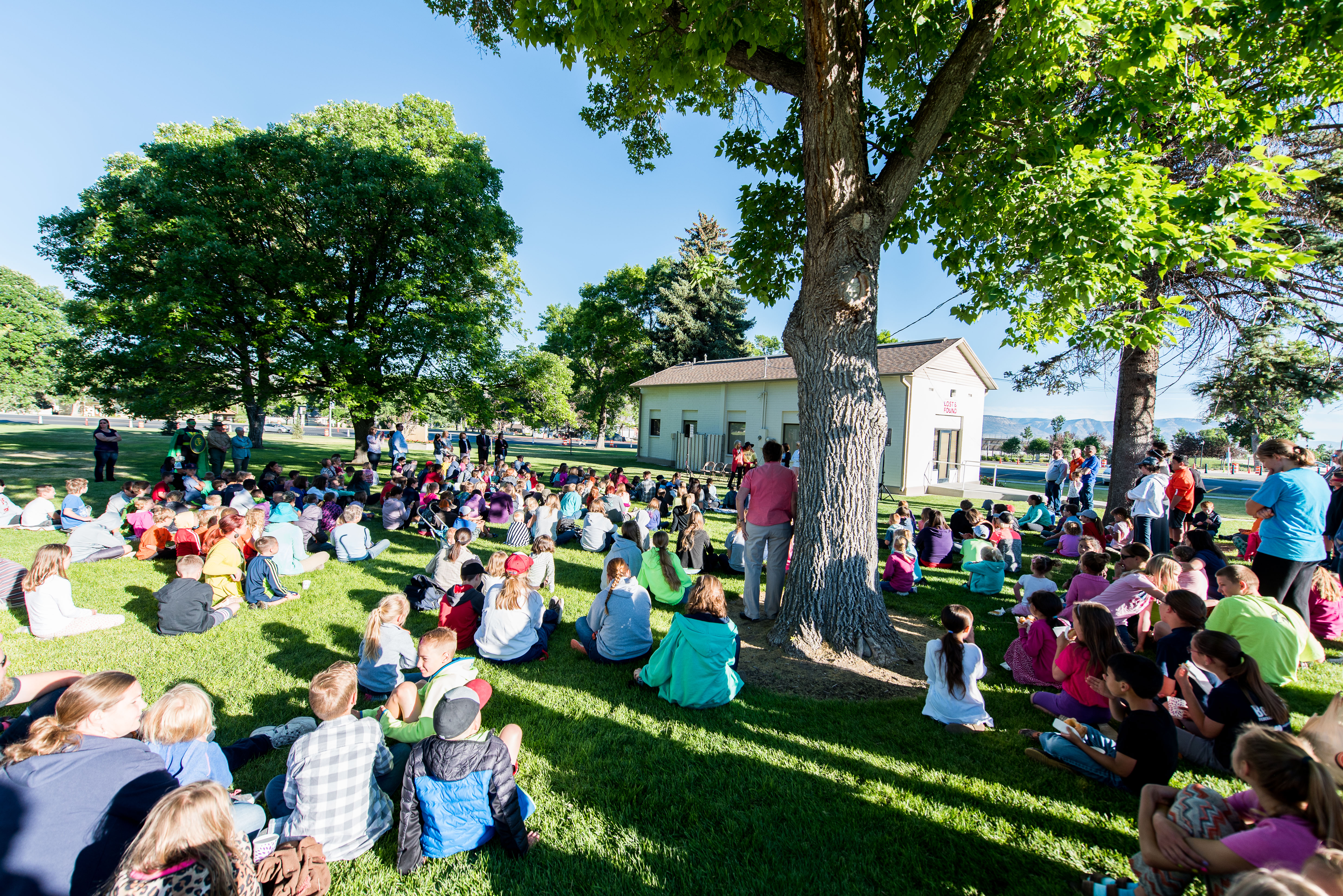 Children and parents gather to hear from Primary general president Joy D. Jones on June 21 after cleaning up the grounds of the Manti Utah Temple across the street.