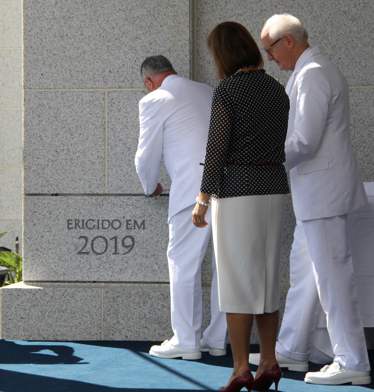 Elder Ulisses Soares of the Quorum of the Twelve Apostles places mortar around the cornerstone of the Fortaleza Brazil Temple on Sunday, June 2, 2019. Sister Rosana Soares, and Elder Larry Y. Wilson, a General Authority Seventy and executive director of the Temple Department, watch.