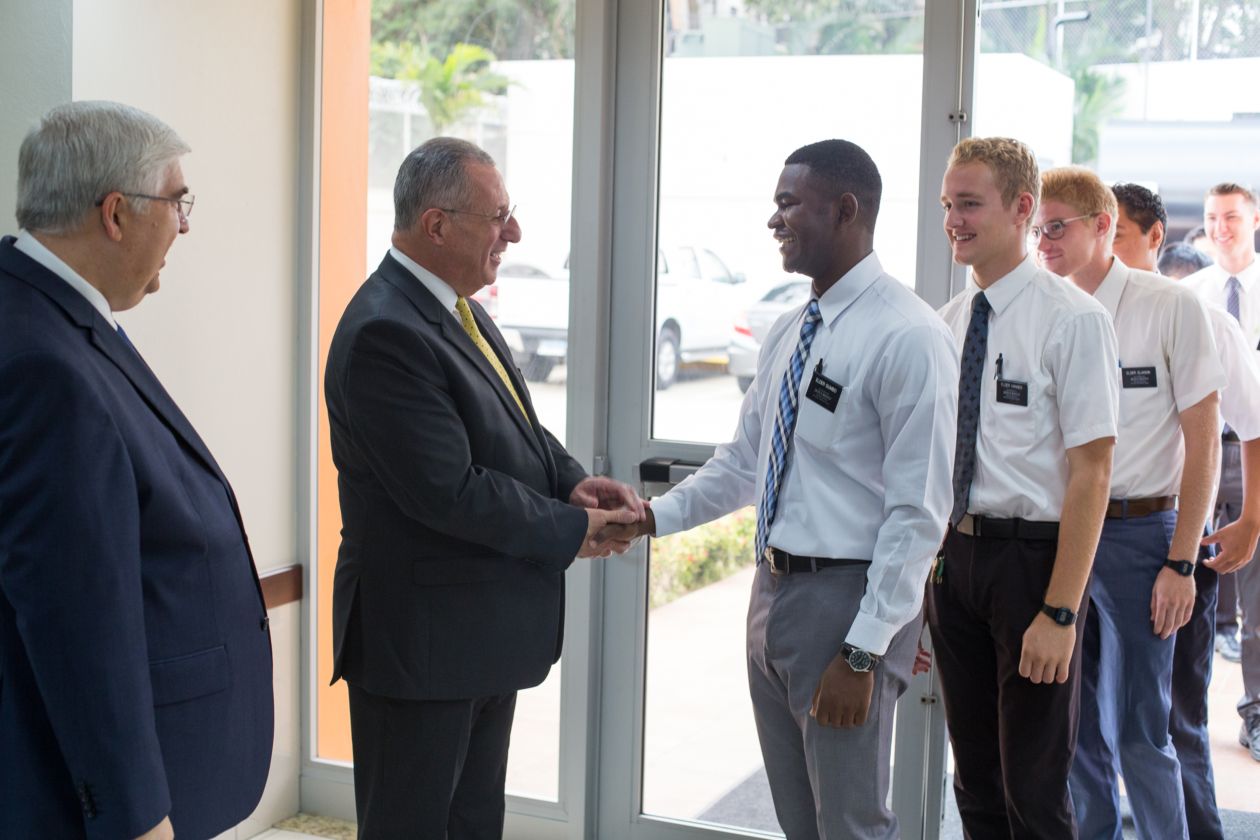 Elder José A. Teixeira and Elder Ulisses Soares greet missionaries from the Santiago Dominican Republic Mission to a Feb. 16 missionary meeting.