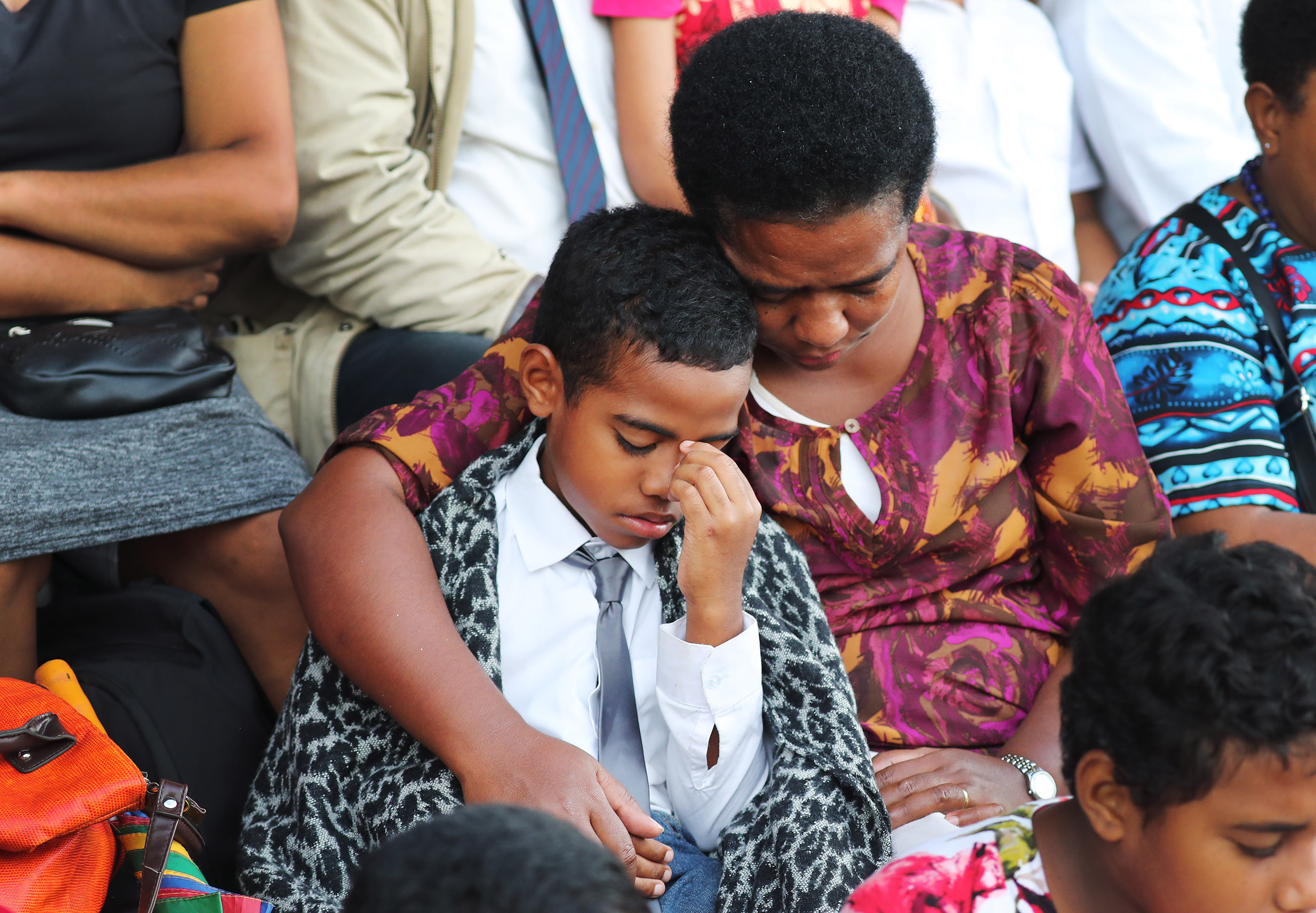 Julie Gaunavinalea and her son Sau bow their heads during the prayer during a devotional at Ratu Cakobau Park stadium in Nausori, Fiji, on May 22, 2019.