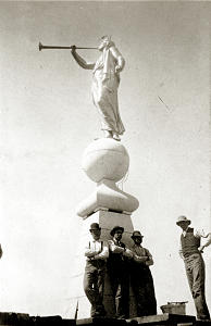 Workers completing Salt Lake Temple in 1893 pose for picture on spire below Cyrus Dallin's sculpture of Moroni.