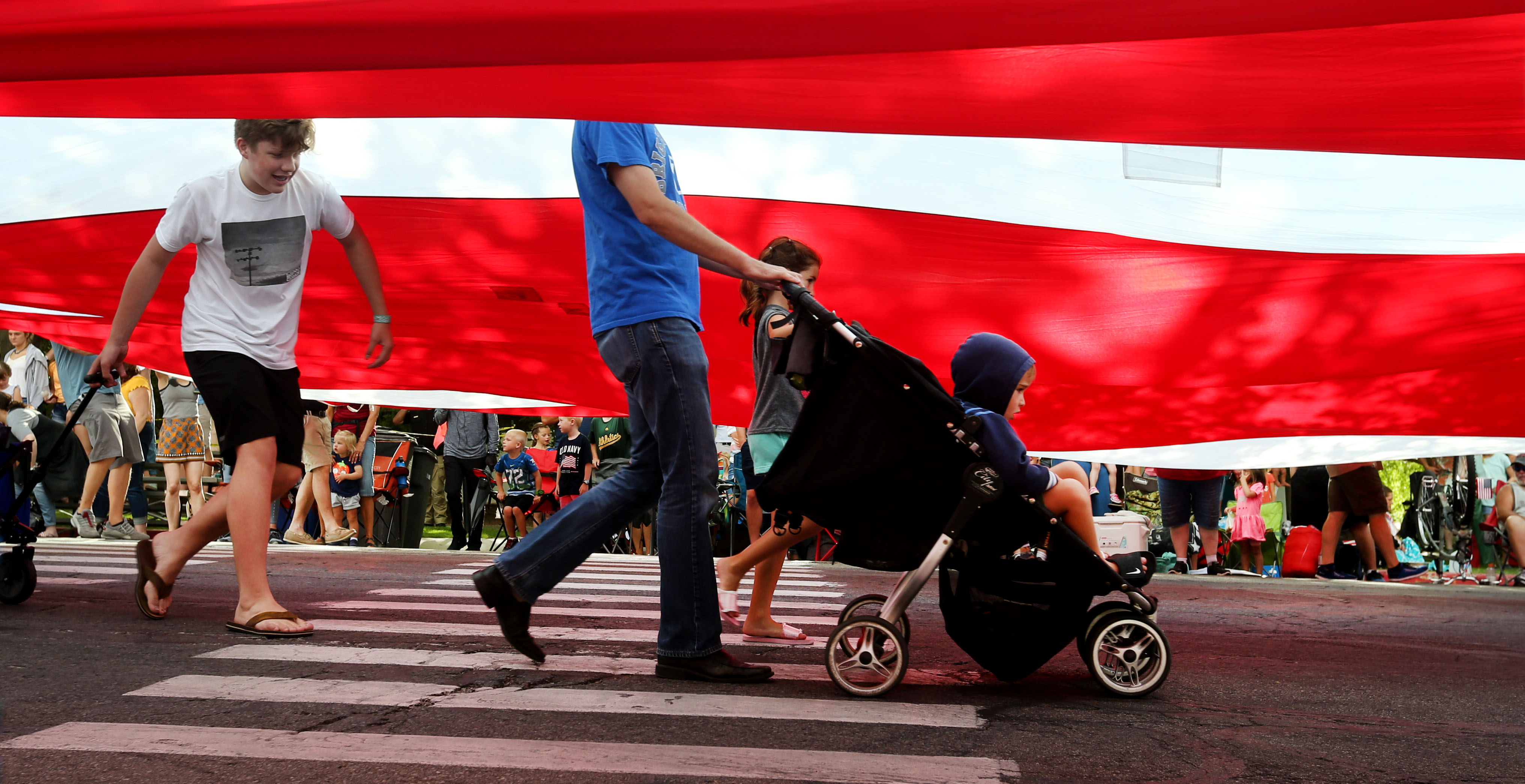 People walk underneath the American flag during the Days of '47 Parade in Salt Lake City on Wednesday, July 24, 2019.