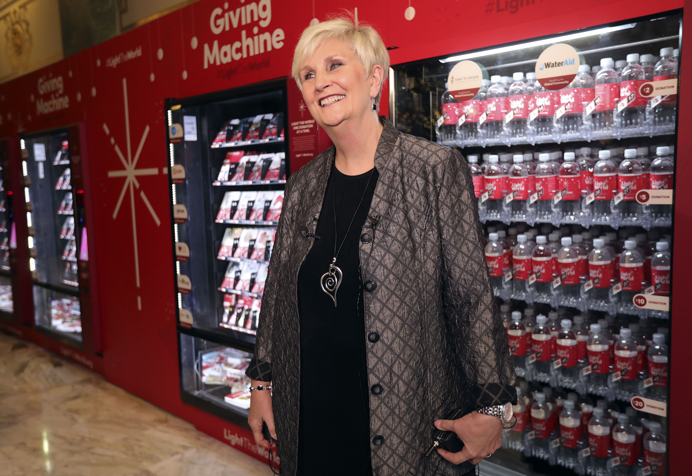 Ginette Bott, president and CEO of the Utah Food Bank, talks about the Light the World Giving Machine in the lobby of the Joseph Smith Memorial Building in Salt Lake City on Wednesday, Nov. 28, 2018.