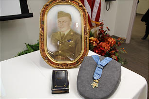 Medal of Honor awarded to Leonard Brostrom, an LDS soldier in World War II, is displayed with his framed portrait during presentation at Church History Library.