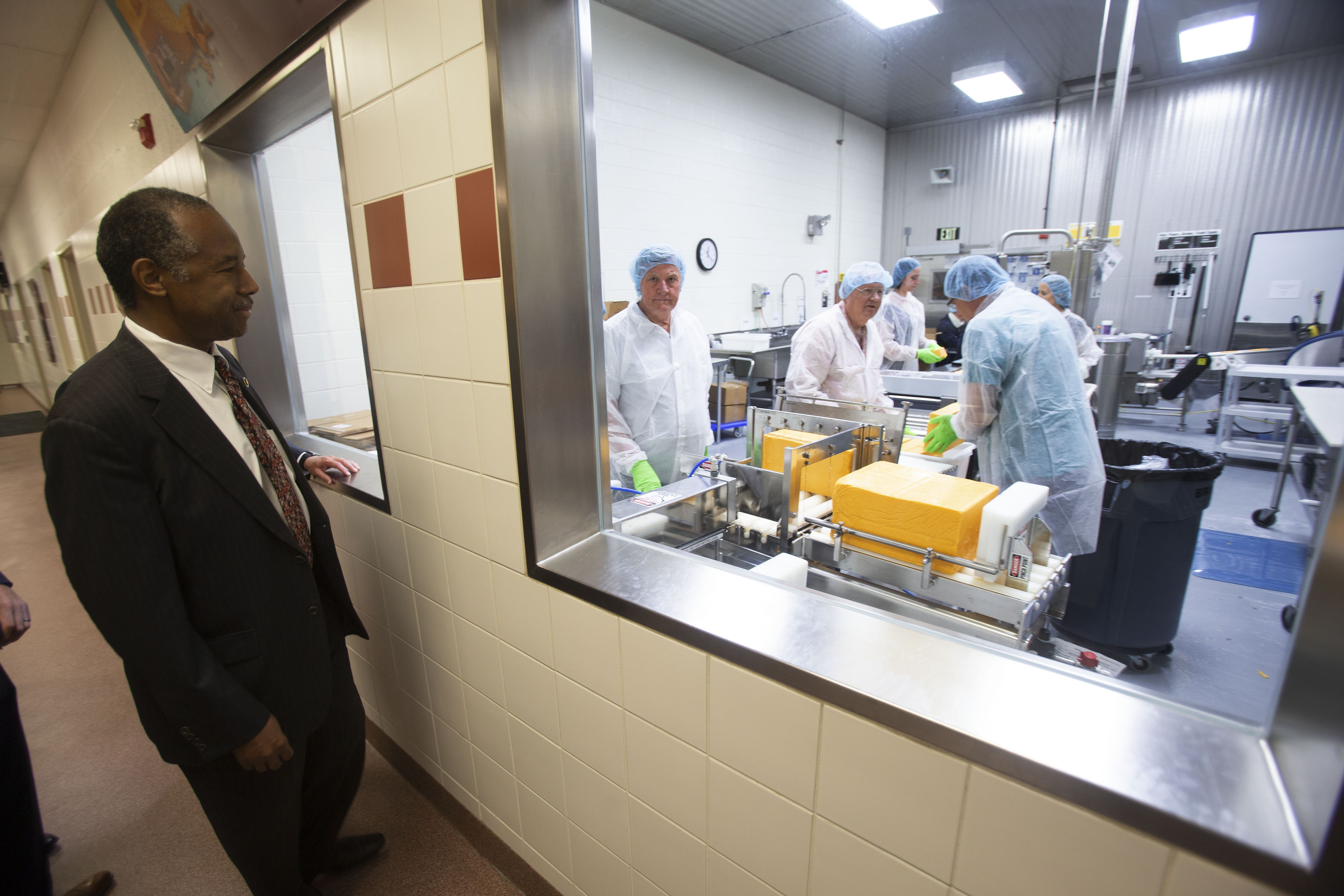 Dr. Ben Carson, secretary of Housing and Urban Development, observes workers processing cheese in the dairy facility at Welfare Square during a Thursday, July 11, 2019, tour in Salt Lake City, Utah.