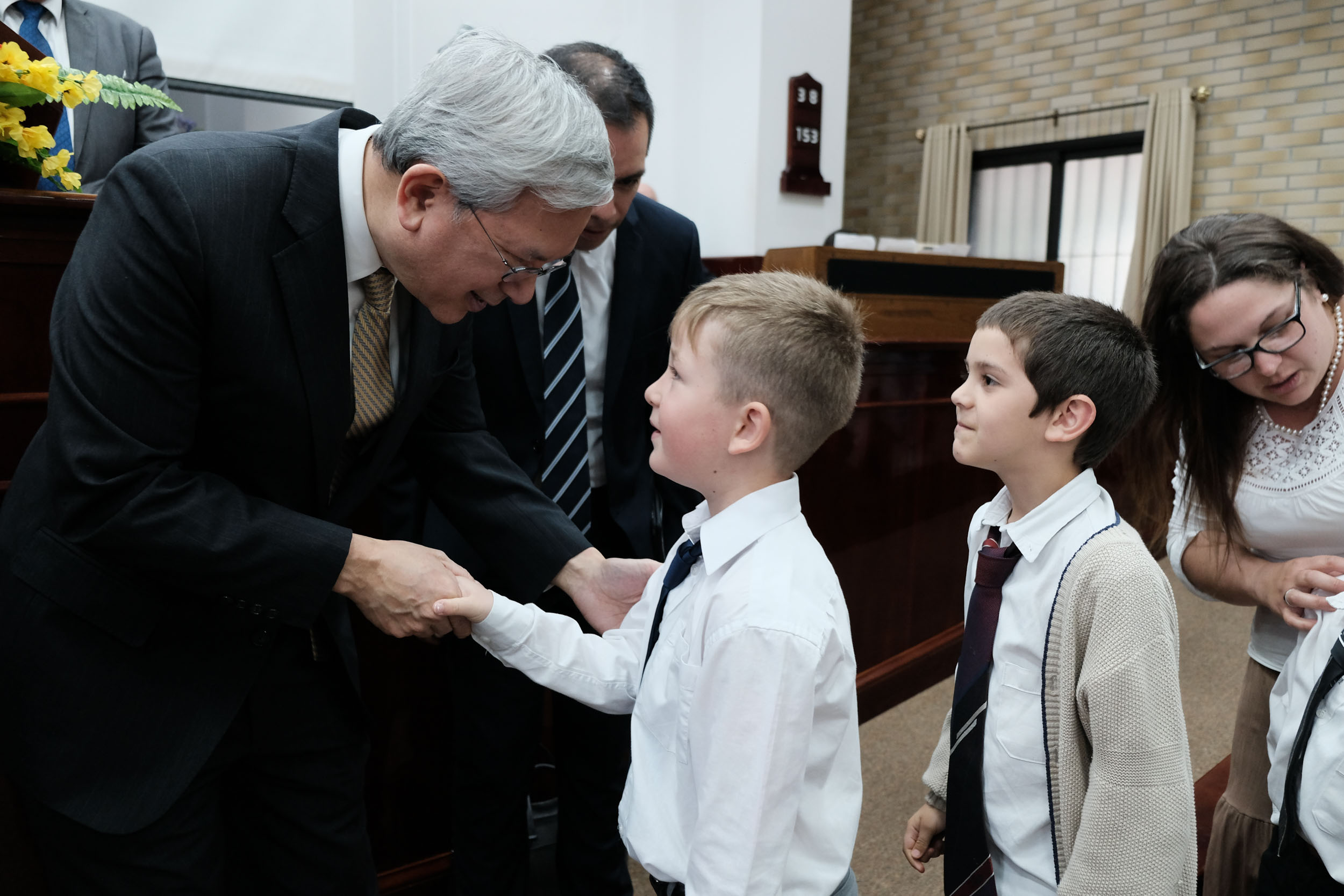 Elder Gong visits with members and children following a meeting in the Florida Uruguay District on Nov. 13. This was the first visit of an Apostle to the District.
