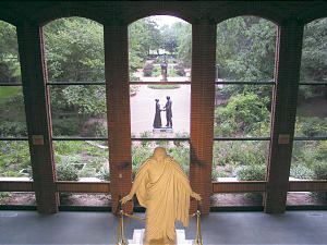 Large windows in the visitors center open to a sweeping view of the women's garden. The setting creates a serene backdrop to the Christus statue.