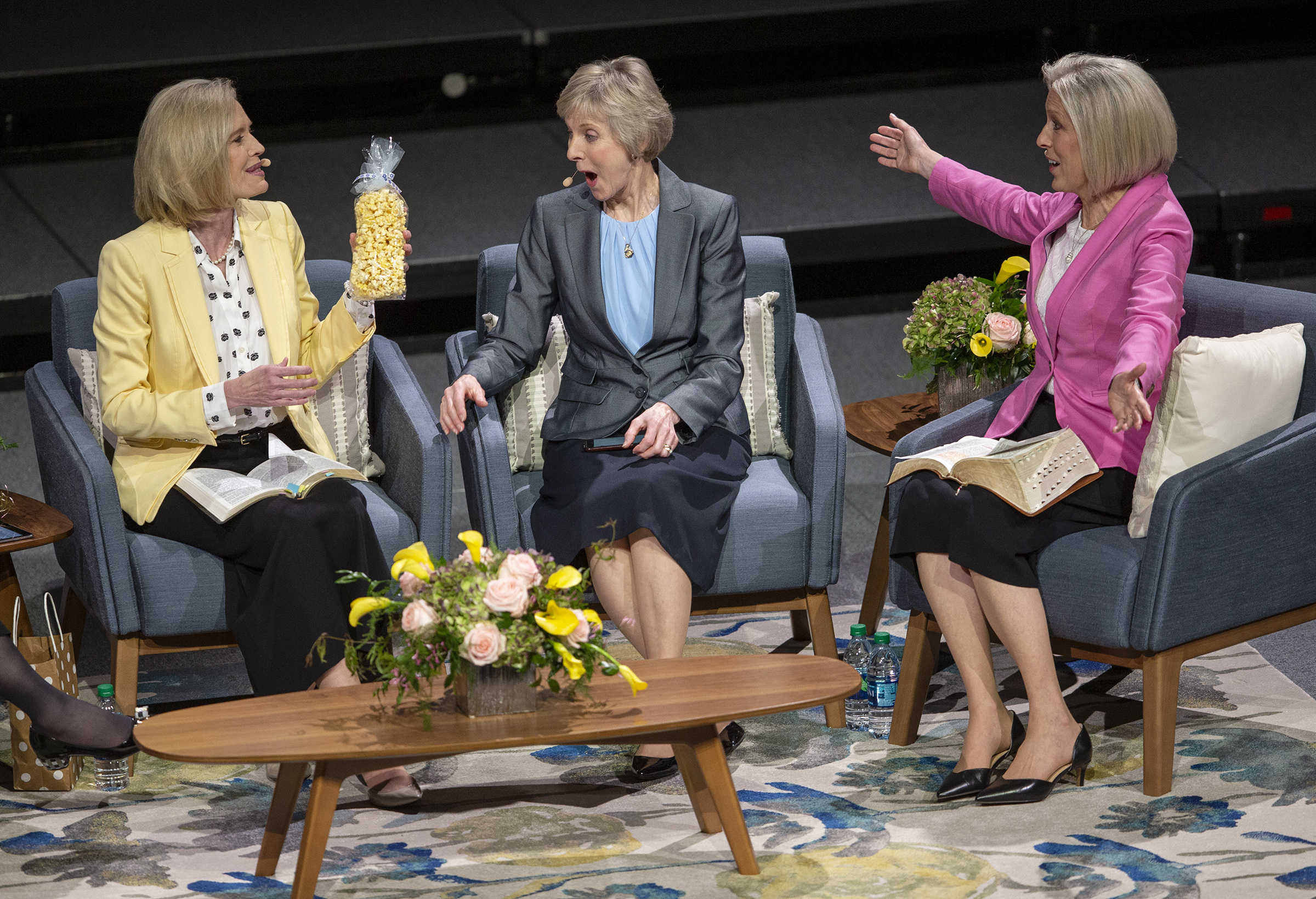 "Sister Bonnie H. Cordon, Young Women general president; holds a bag of popcorn before giving it to Sister Joy D. Jones, Primary general president, who reacts to the gift as Sister Jean B. Bingham, Relief Society general president, reacts as well during a ""Sister to Sister"" event at Women's Conference at BYU's Marriott Center in Provo, Utah, on Friday, May 3, 2019."
