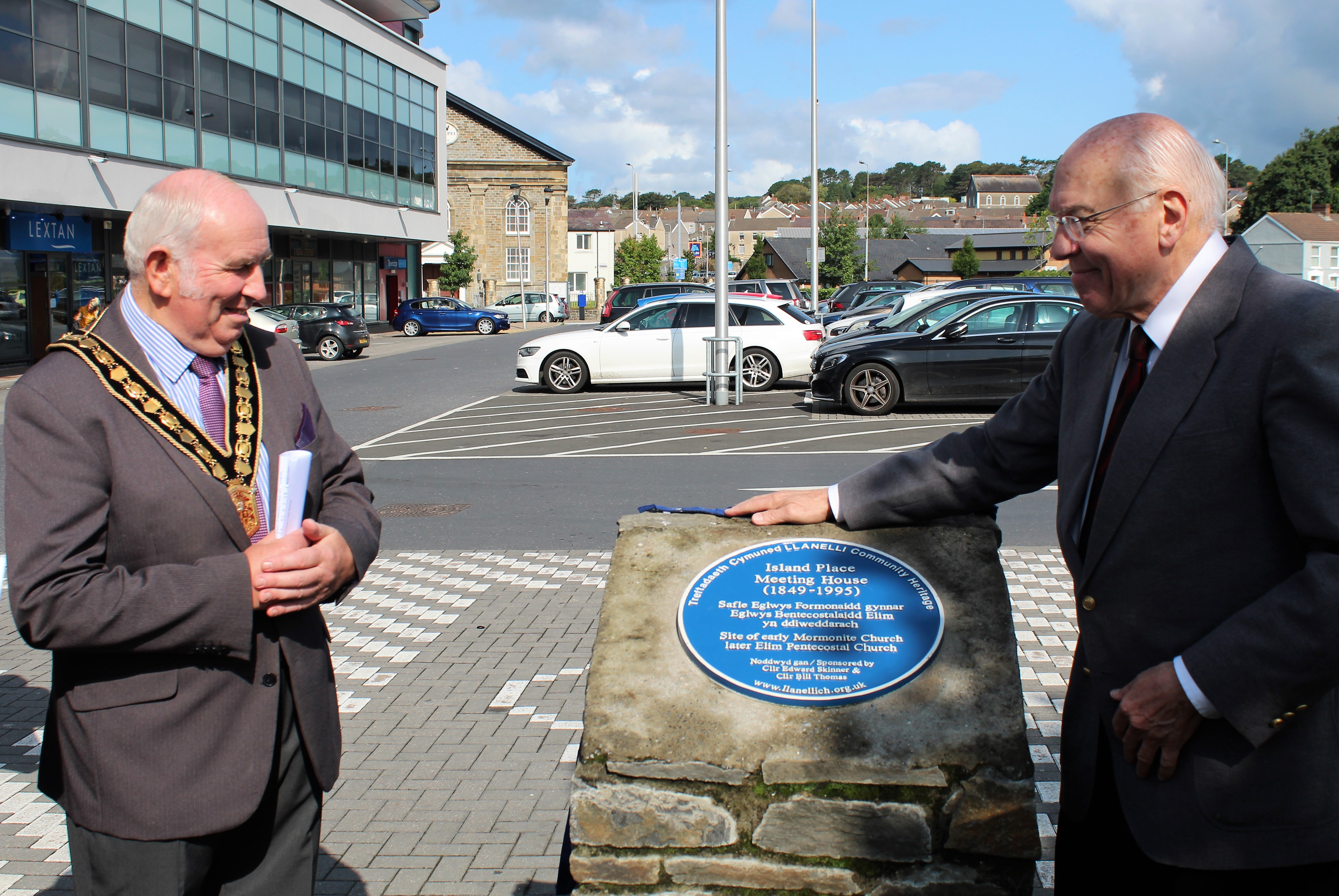 On the right, Dr. Ronald Dennis unveils the blue plaque to commemorate the historic Island Place Meeting House in Llanelli, Wales. On the left stands the Chair of the Carmathenshire County Council, Councilor Mansel Charles, Plaid Cymru of Llanegwad on Aug. 25, 2018.