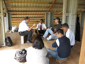 Church members gather outside Banda Aceh, Indonesia, at construction yard where concrete panels for houses are manufactured. From left, tsunami director William Reynolds; Elder Subandriyo, Area Seventy; Ron Felt, project contractor; Sutarno, local contractor; and Hendro and Bertha, Indonesia public affairs, discuss Church project.