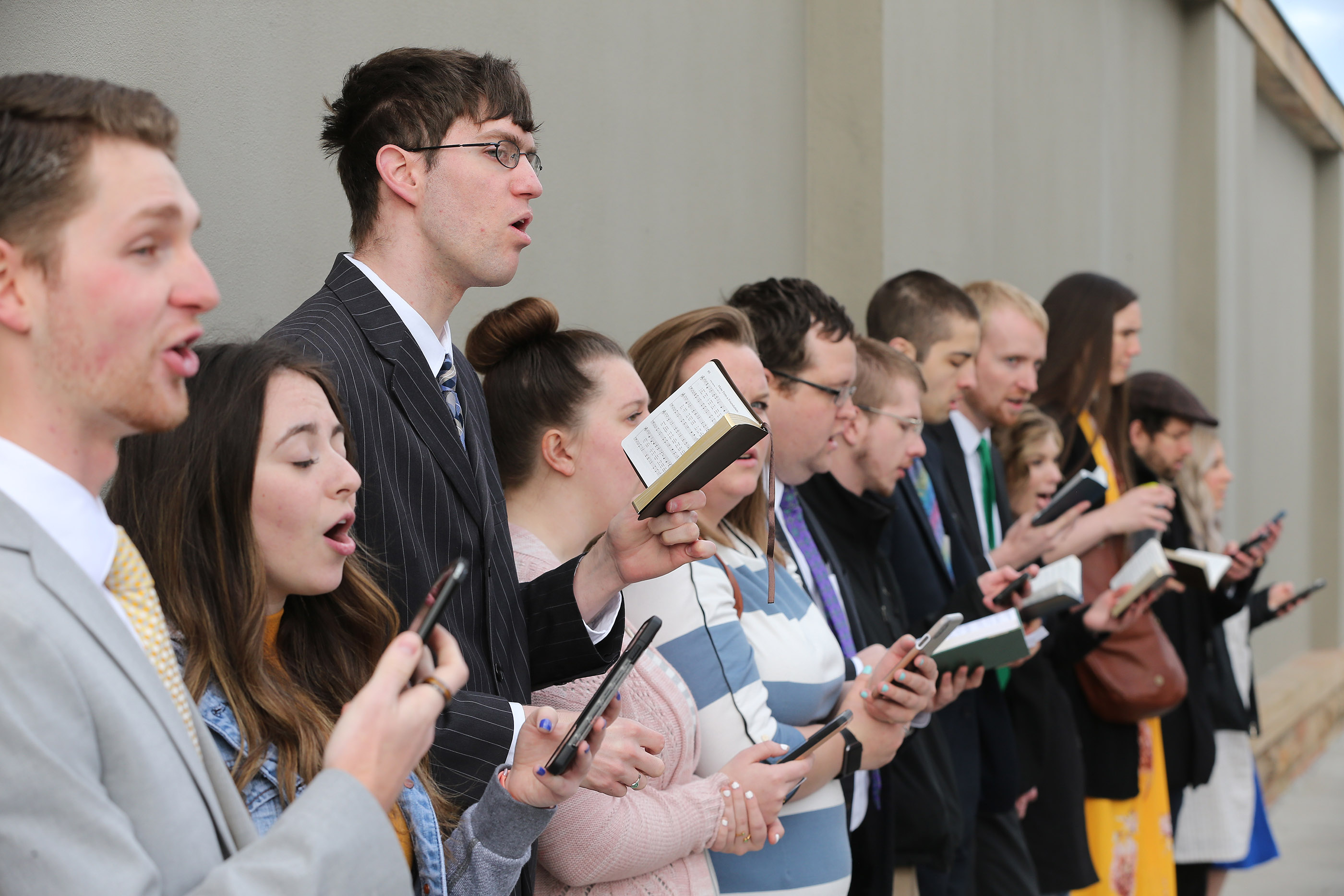 Conferencegoers sing outside at the Conference Center prior to the Sunday morning session of the 189th Annual General Conference of The Church of Jesus Christ of Latter-day Saints in Salt Lake City on Sunday, April 7, 2019.
