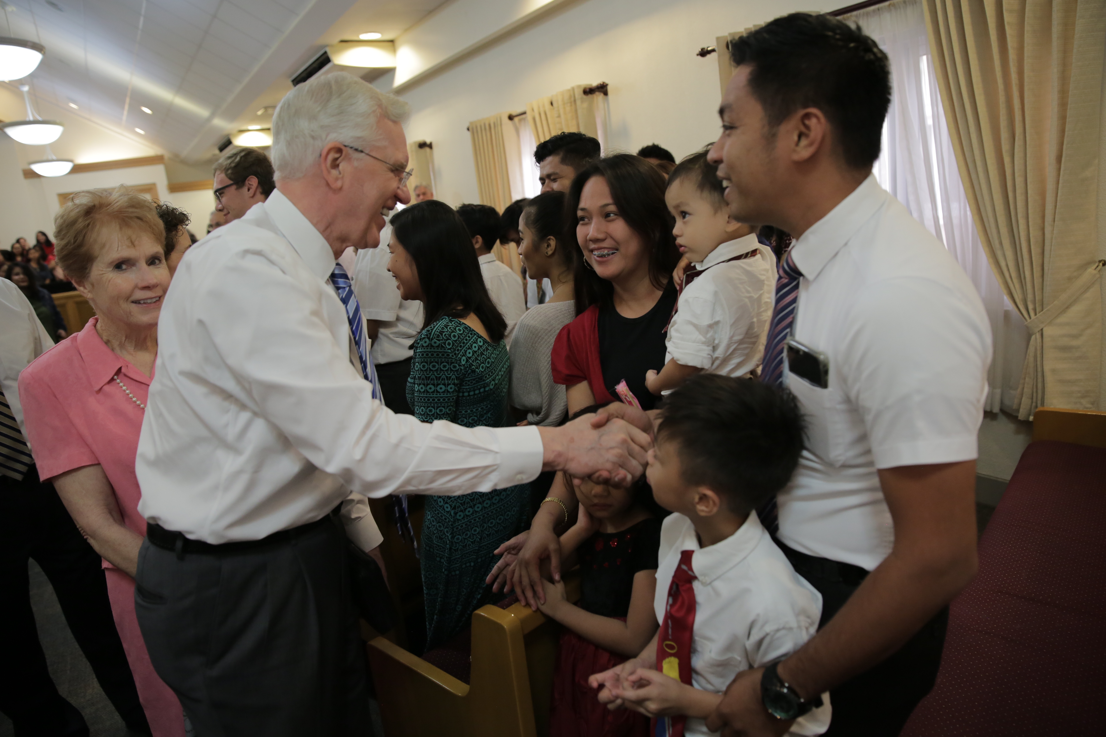 Elder D. Todd Christofferson and Sister Kathy Christofferson greet families during recent tour of the Philippines.