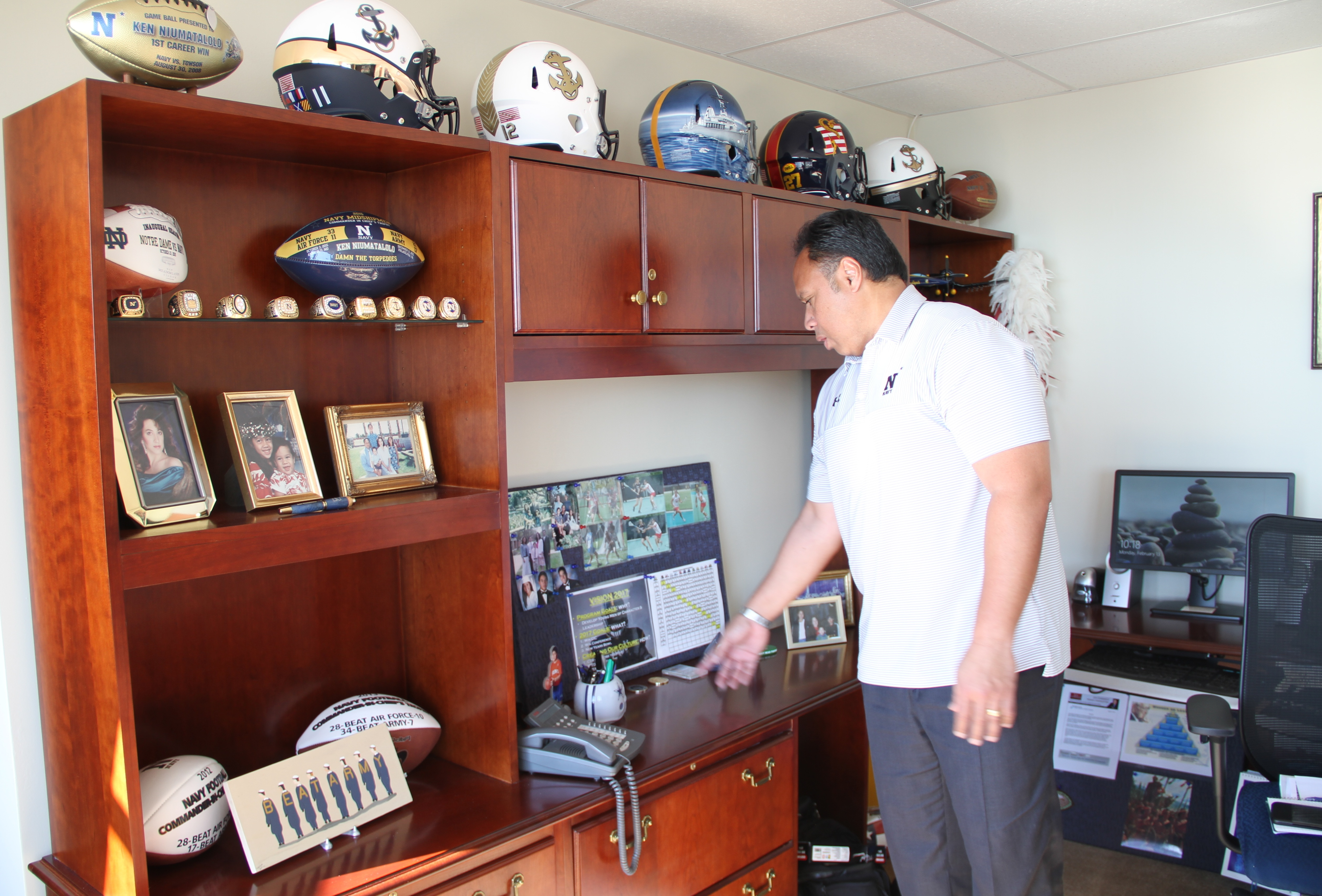 Multi-layed shelf in Navy coach Ken Niumatalolo's office is adorned with football helmets and other memorabilia reflective of his success at the U.S. service academy in Annapolis.