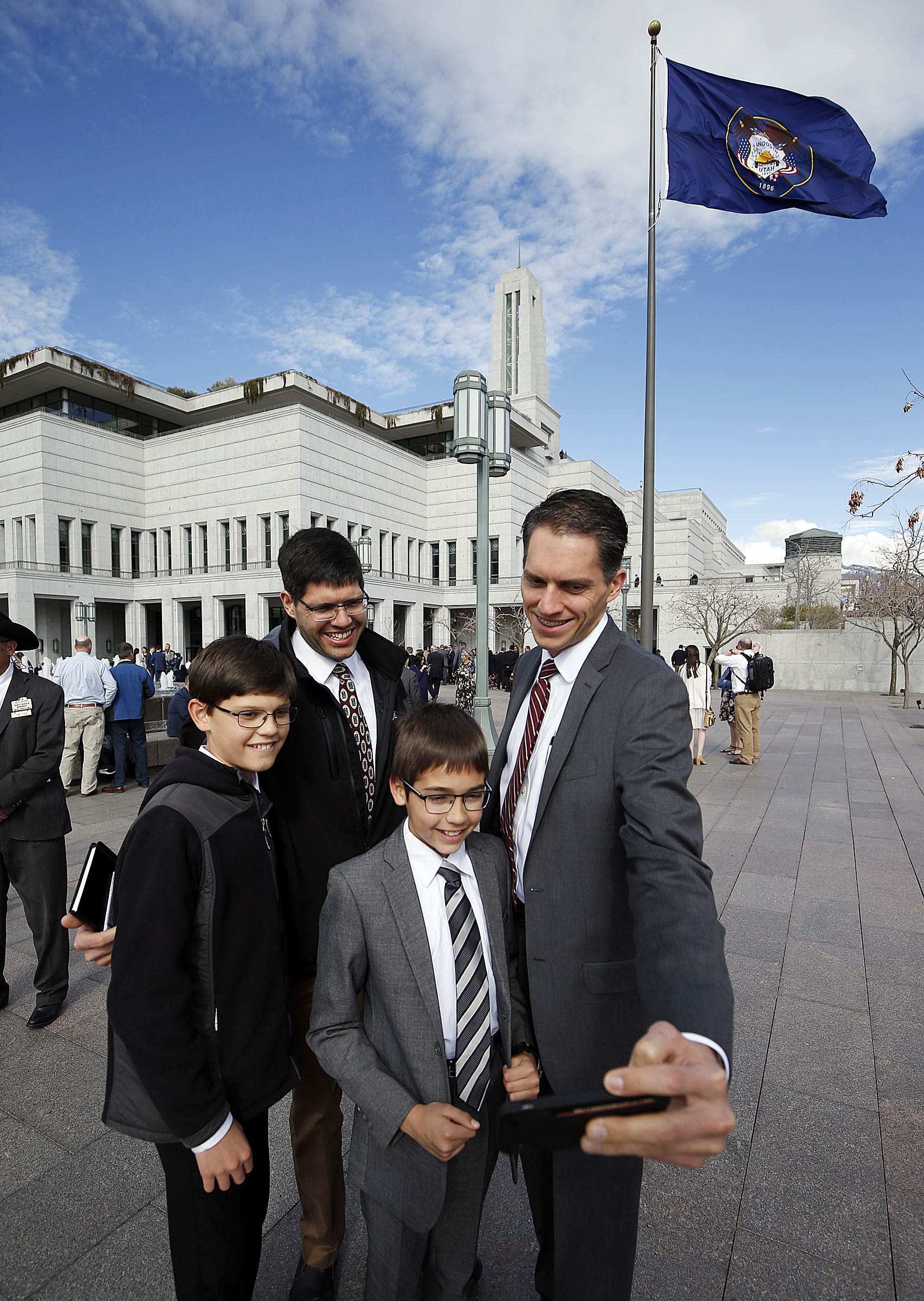 Steve Spigarelli, right, his son, Henry, his brother, David, and David's son, Daniel, take a photo before the 189th Annual General Conference of The Church of Jesus Christ of Latter-day Saints outside the Conference Center in Salt Lake City on Saturday, April 6, 2019.