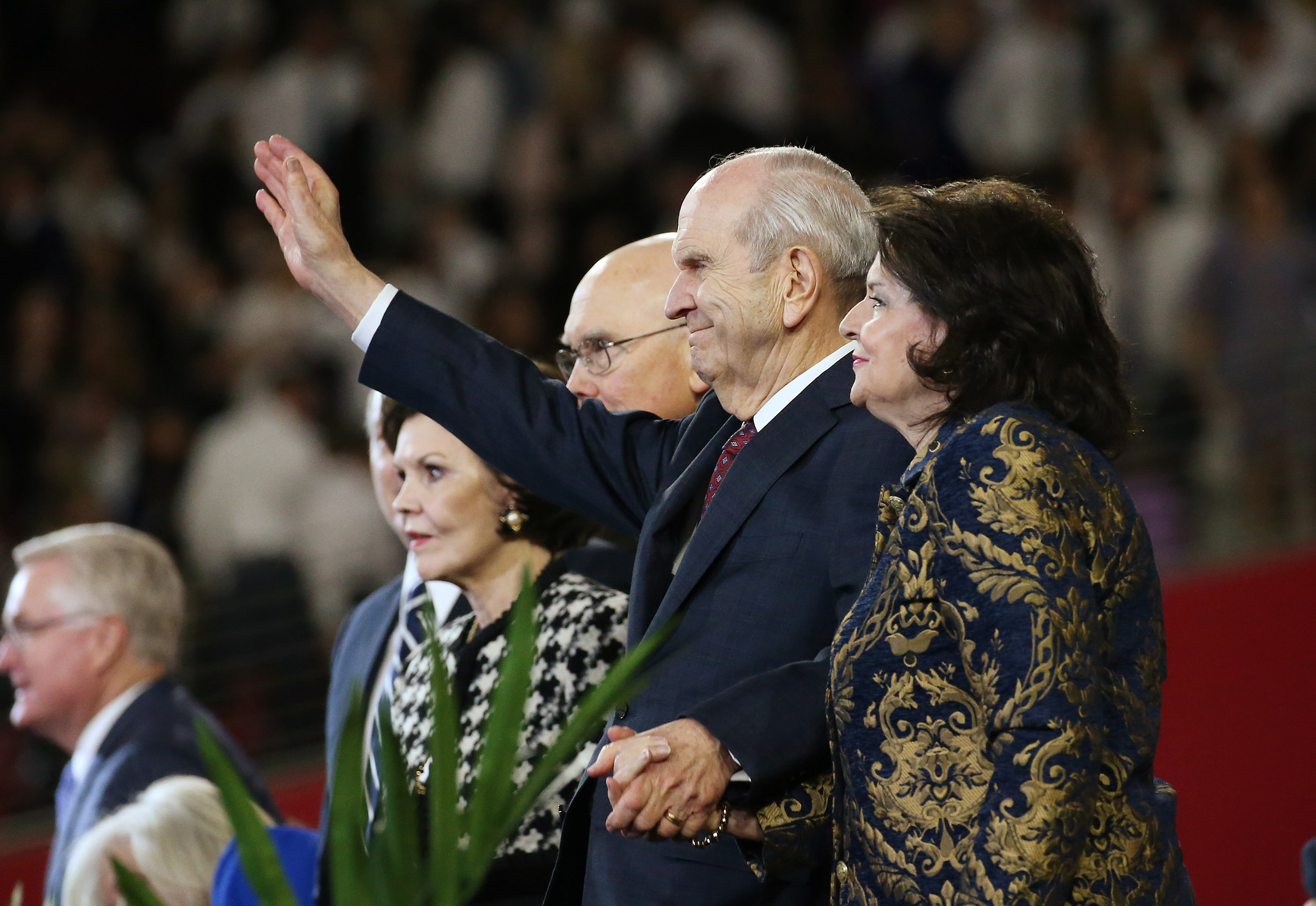 President Russell M. Nelson of The Church of Jesus Christ of Latter-day Saints waves to attendees with his wife, Sister Wendy Nelson, after a devotional at the State Farm Stadium in Phoenix on Sunday, Feb. 10, 2019.