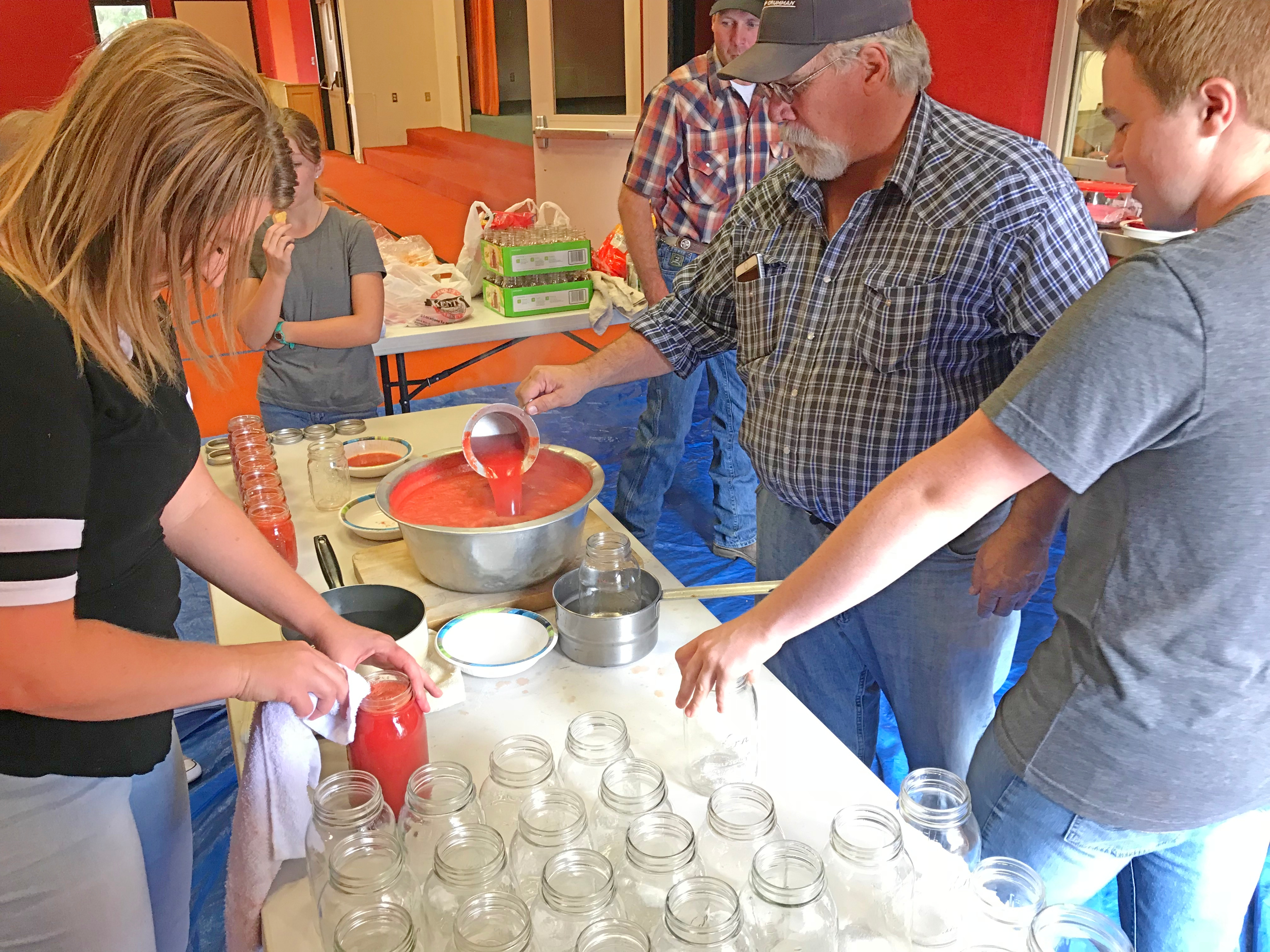 Center, Alan Johnson, first counselor in the Howell Ward bishopric, prepares to pour tomato juice into a bottle during a youth canning activity at the Howell Community Center on Saturday, Sept. 8, 2018.