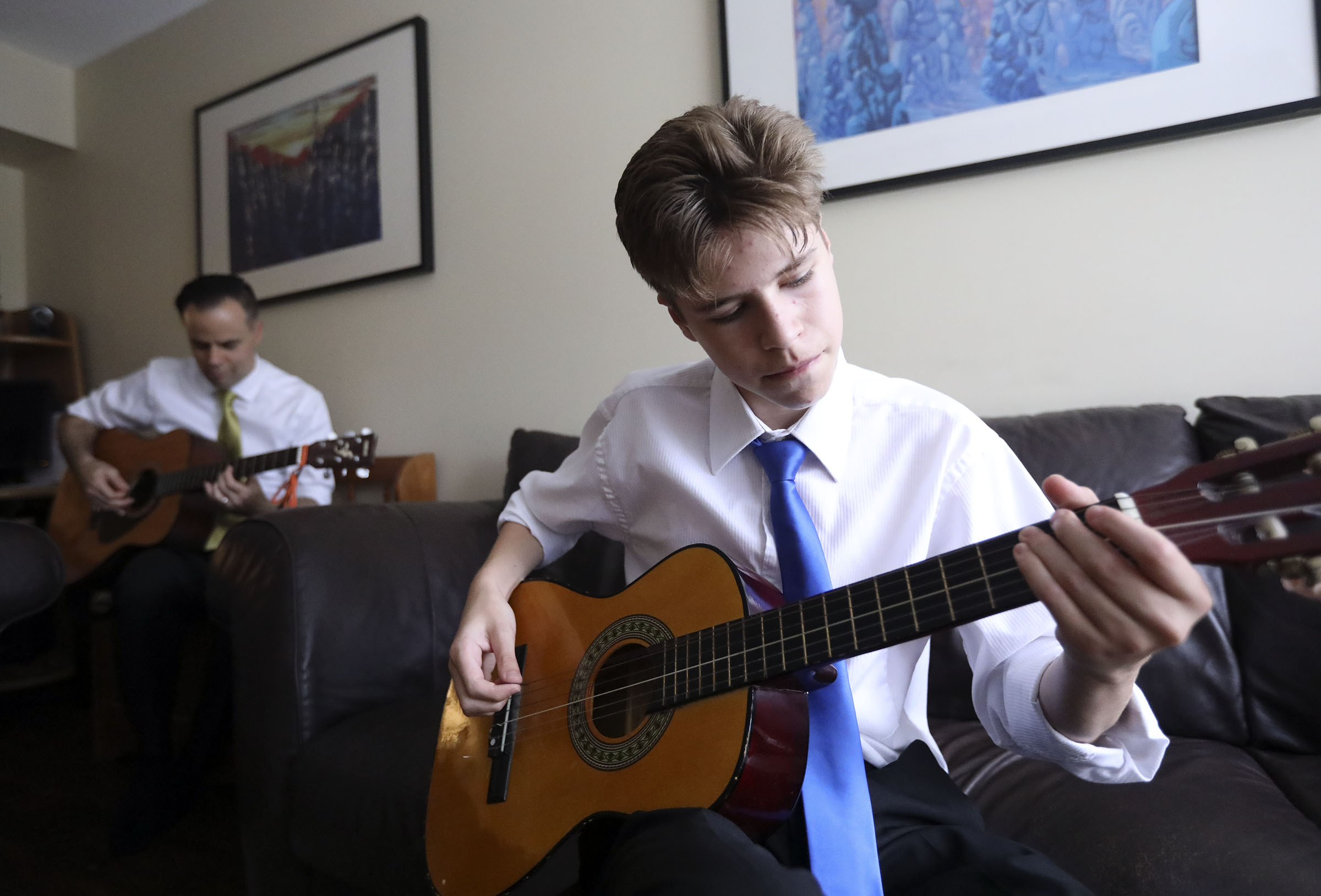Scott Friesen and his son Zach Friesen play guitar at home in Langley, British Columbia, on Sunday, Sept. 16, 2018.