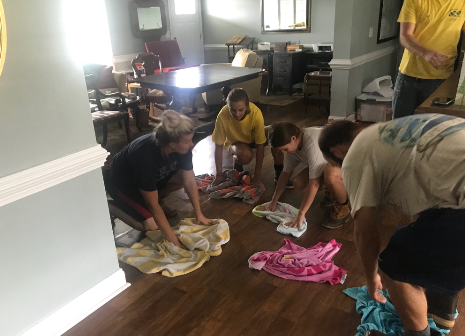 Members of the Harkers Island Ward clean up the floor of a home damaged by Hurricane Florence, serving on Sunday, Sept. 16, 2018.