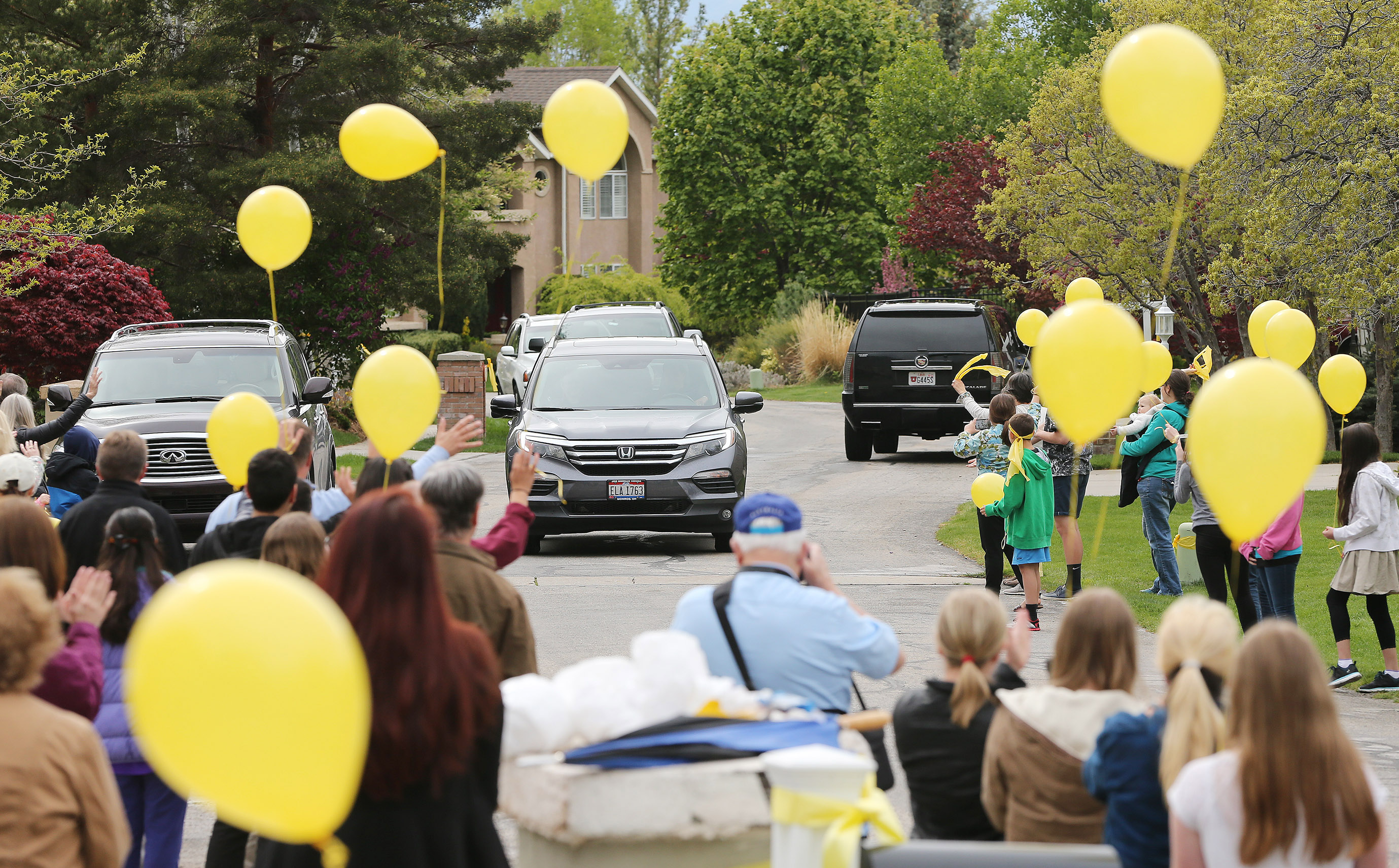 Neighbors line the street and wave as Elder Mason Wells returns home in Sandy Thursday, April 28, 2016 after sprending 37 days in the hospital after being injured in the Brussels terrorist attack.