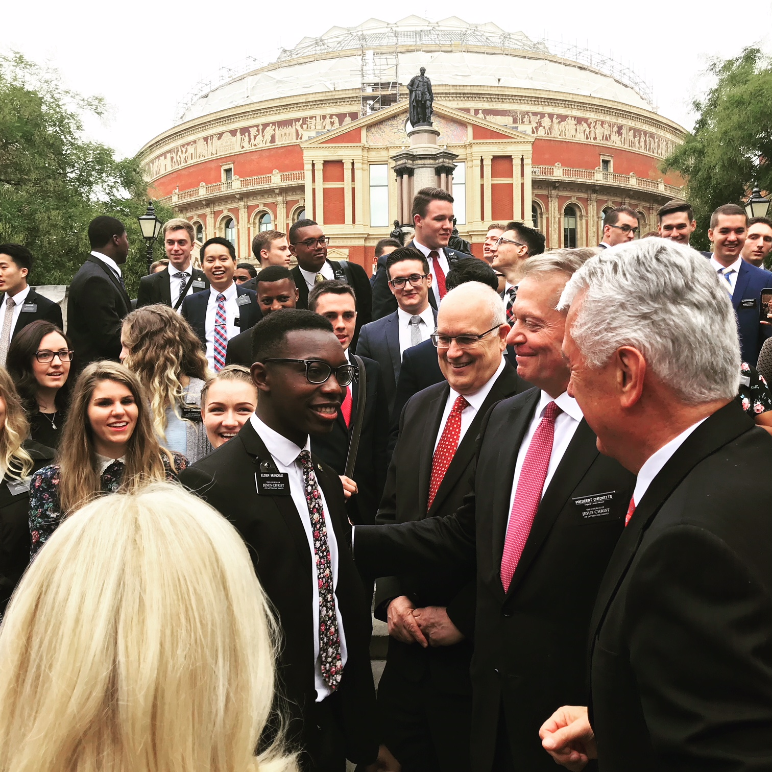 Elder Dieter F. Uchtdorf, right, of the Quorum of the Twelve Apostles, joins President David W. Checketts of the England London Mission in greeting some of the mission's missionaries after a group photo outside London's Royal Albert Hall on Sept. 8, 2018.