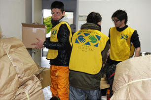 """Clad in """"Helping Hands"""" vests, Church members unload blankets and other supplies at the Nagamachi Ward, Sendai Japan Stake. The supplies will help disaster victims."""