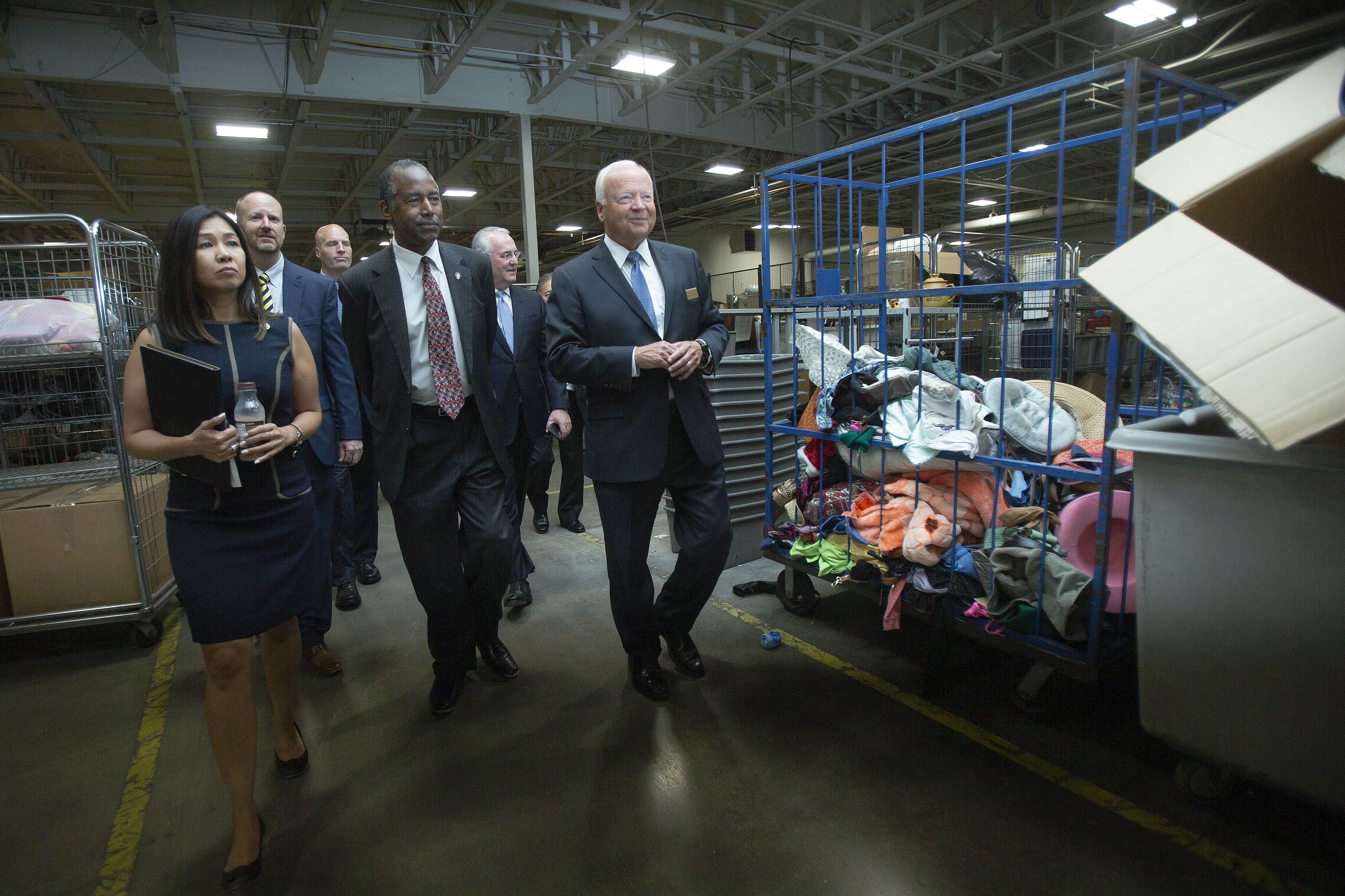 Elder Kent F. Richards, right, walks Dr. Ben Carson, HUD secretary, center, through a Deseret Industries sorting area during a Welfare Square tour Thursday, July 11, 2019, in Salt Lake City.
