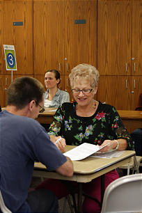 Karen Breckon, donor drive organizer, helps a participant with paperwork. Sister Breckon organized the drive in an attempt to find a stem cell match for Phyllis Roberts, a stake member who suffers from Leukemia.