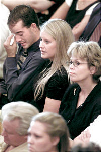Solemn faces and tear-filled eyes are part of memorial service.