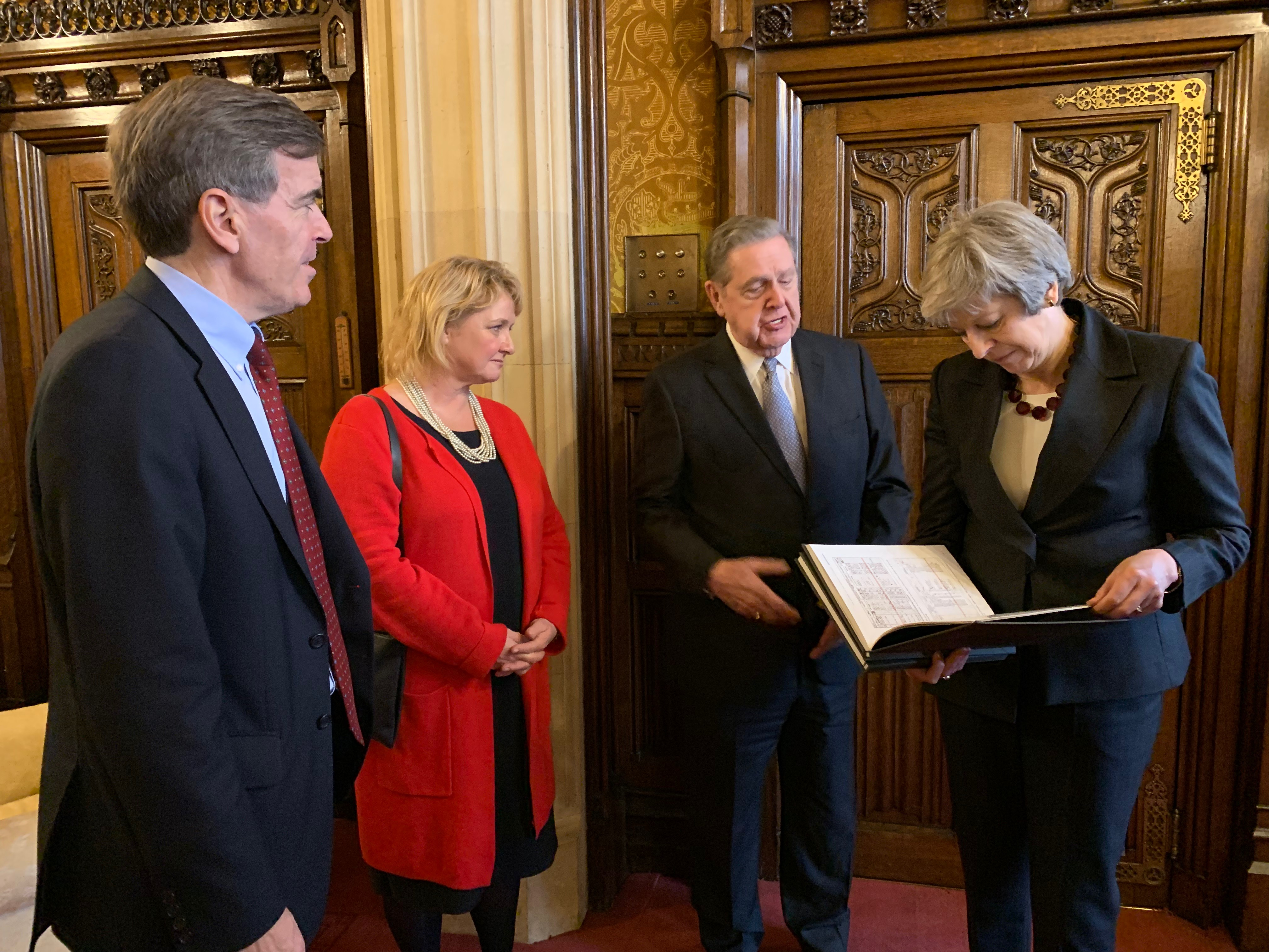 Elder Jeffrey R. Holland of the Quorum of the Twelve Apostles shows British Prime Minister Theresa May a bound copy of her family history records, including photographs of census and marriage records, as David Rutley, a member of Parliament, and Yvonne Kerr, wife of Stephen Kerr, a member of Parliament, look on at the Palace of Westminster on Wednesday, Nov. 21, 2018.