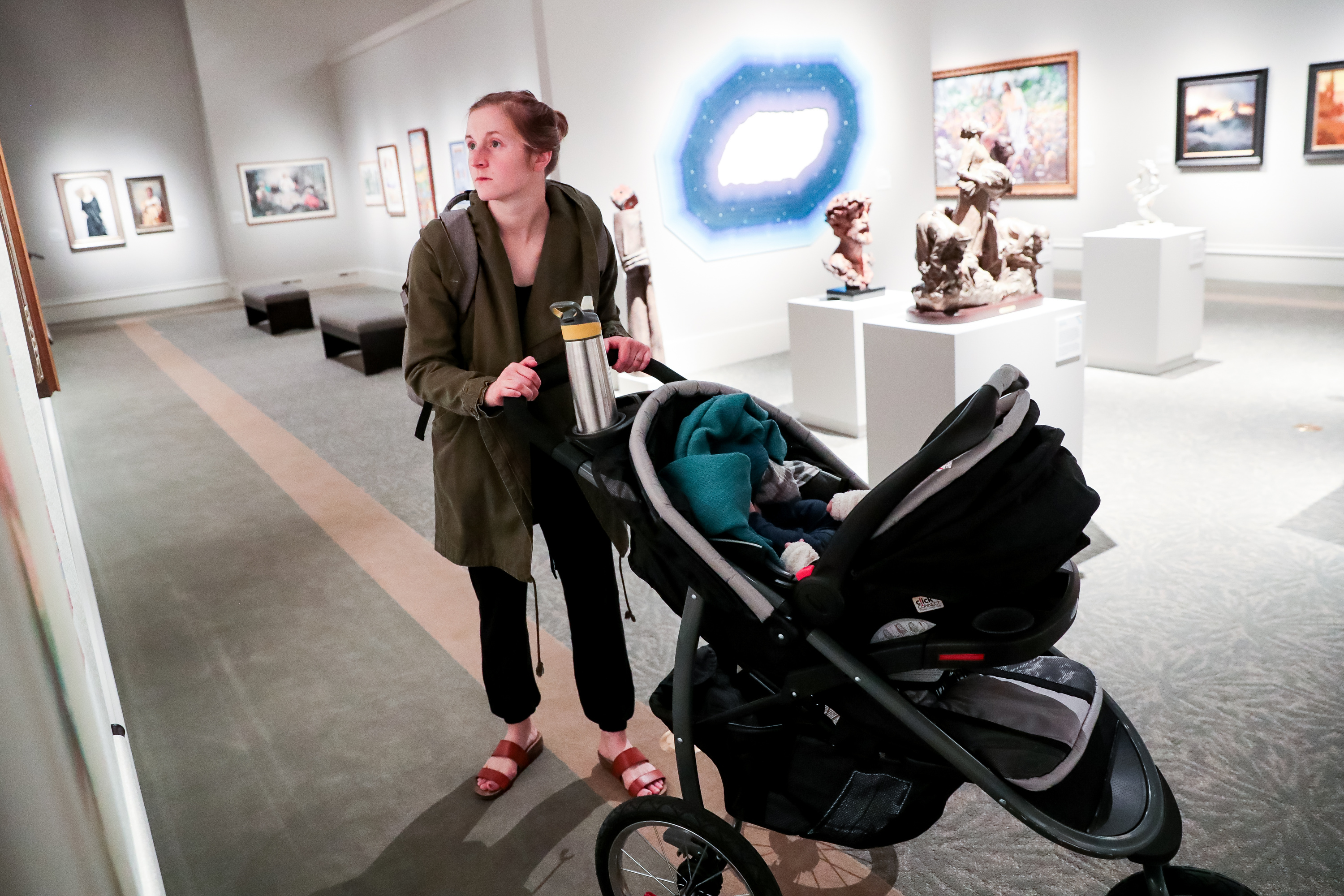 """Sarah Anne Winegar, of Springville, and her 3-month-old son, Luca, tour the 11th International Art Exhibition at the Church History Museum during a media preview in Salt Lake City on Tuesday, March 12, 2019. Winegar has a relief reduction print titled """"Come Unto Me,"""" included in the exhibit."""