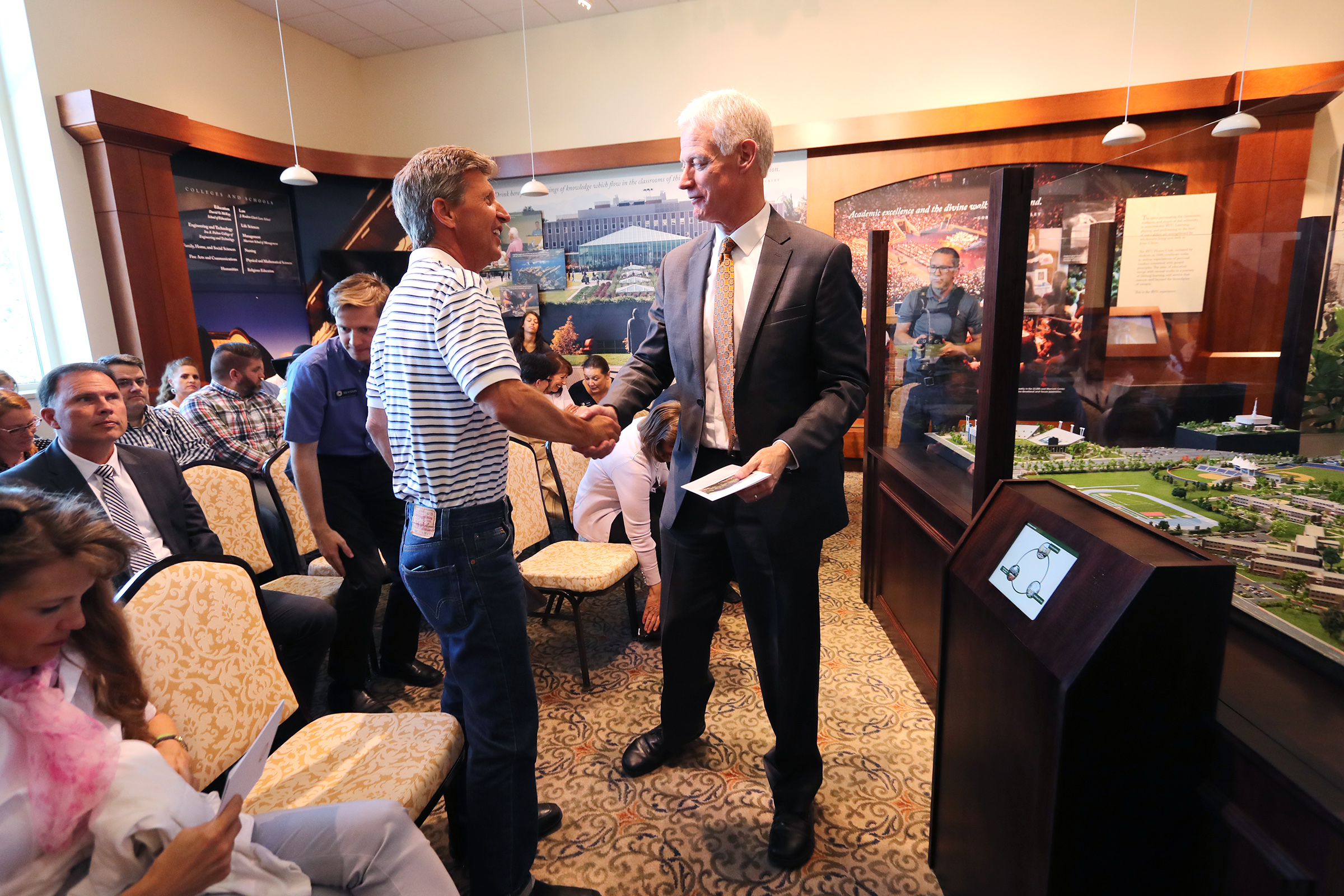 John L. Sorensen and BYU President Kevin J Worthen shake hands as unveils a highly-detailed campus diorama on Tuesday, July 2, 2019.