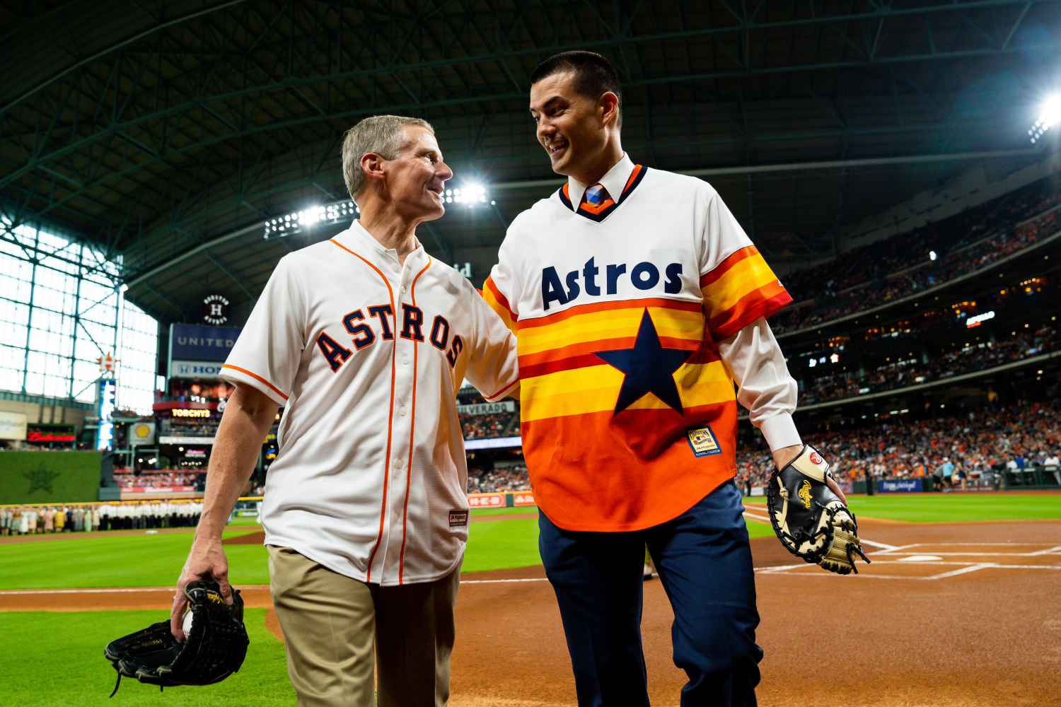 Elder David A. Bednar and President Jeremy Guthrie congratulating each other for a successful first pitch.