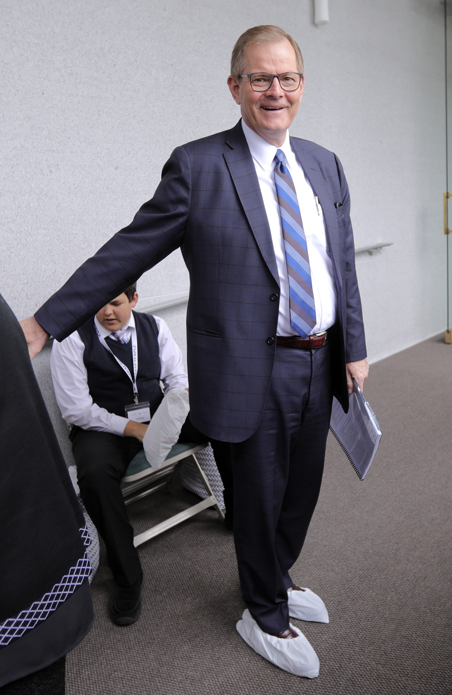 Elder Gary E. Stevenson, of the Quorum of the Twelve Apostles, puts shoe covers on before touring the newly renovated Oakland California Temple, of The Church of Jesus Christ of Latter-day Saints, in Oakland, Calif., on Monday, May 6, 2019.
