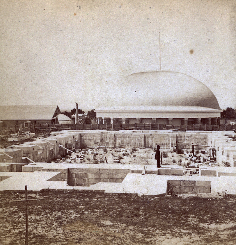 The foundation of the Salt Lake Temple is visible in the foreground with the Tabernacle in the background during construction in about 1868.