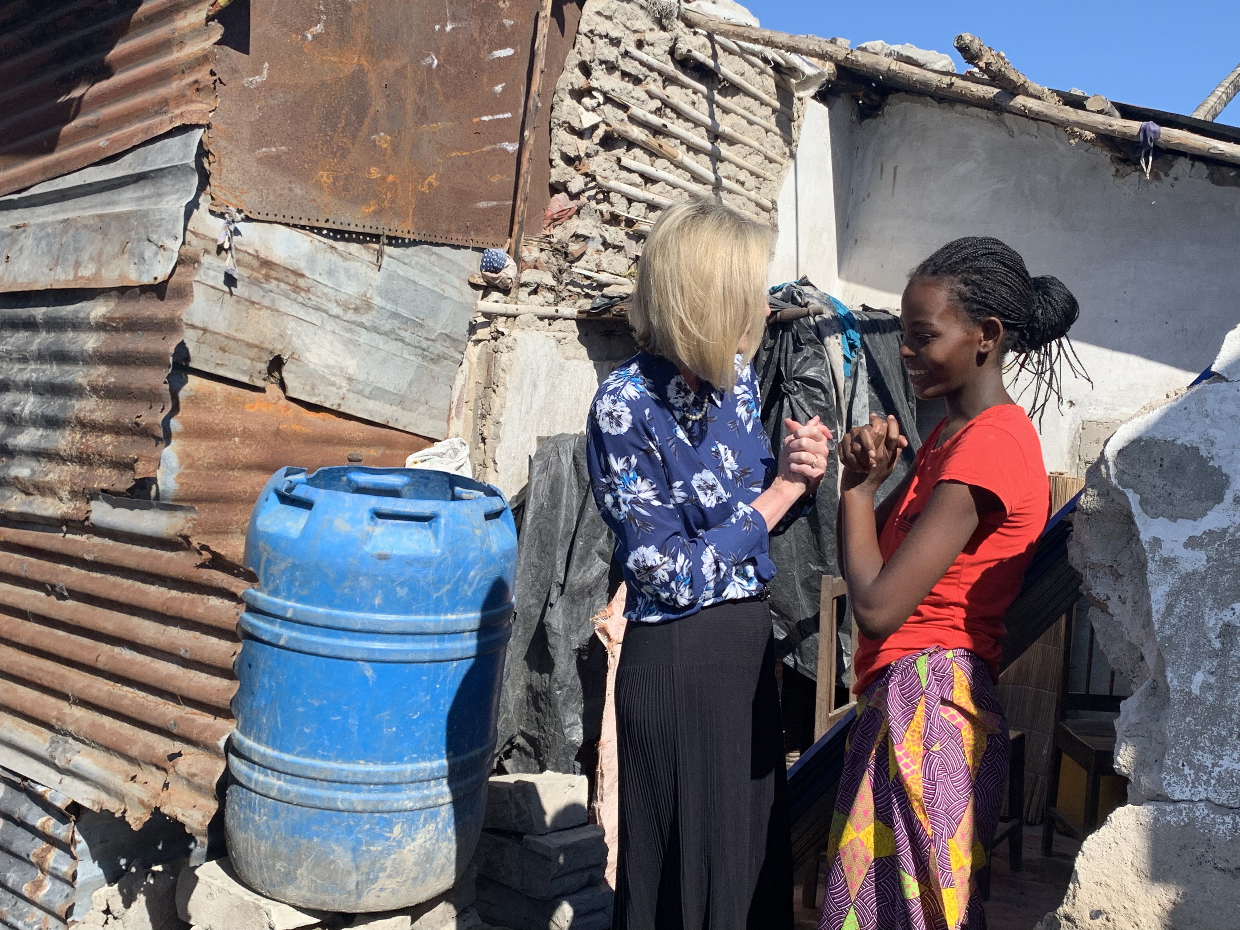 Sister Bonnie H. Cordon speaks with a young girl in Beira, Mozambique while visiting the homes of members that were destroyed in a recent cyclone in the area.